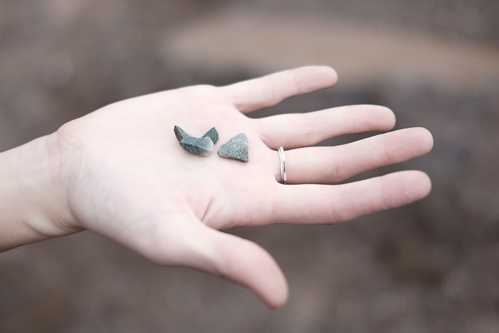 three gray pebbles on person's palm