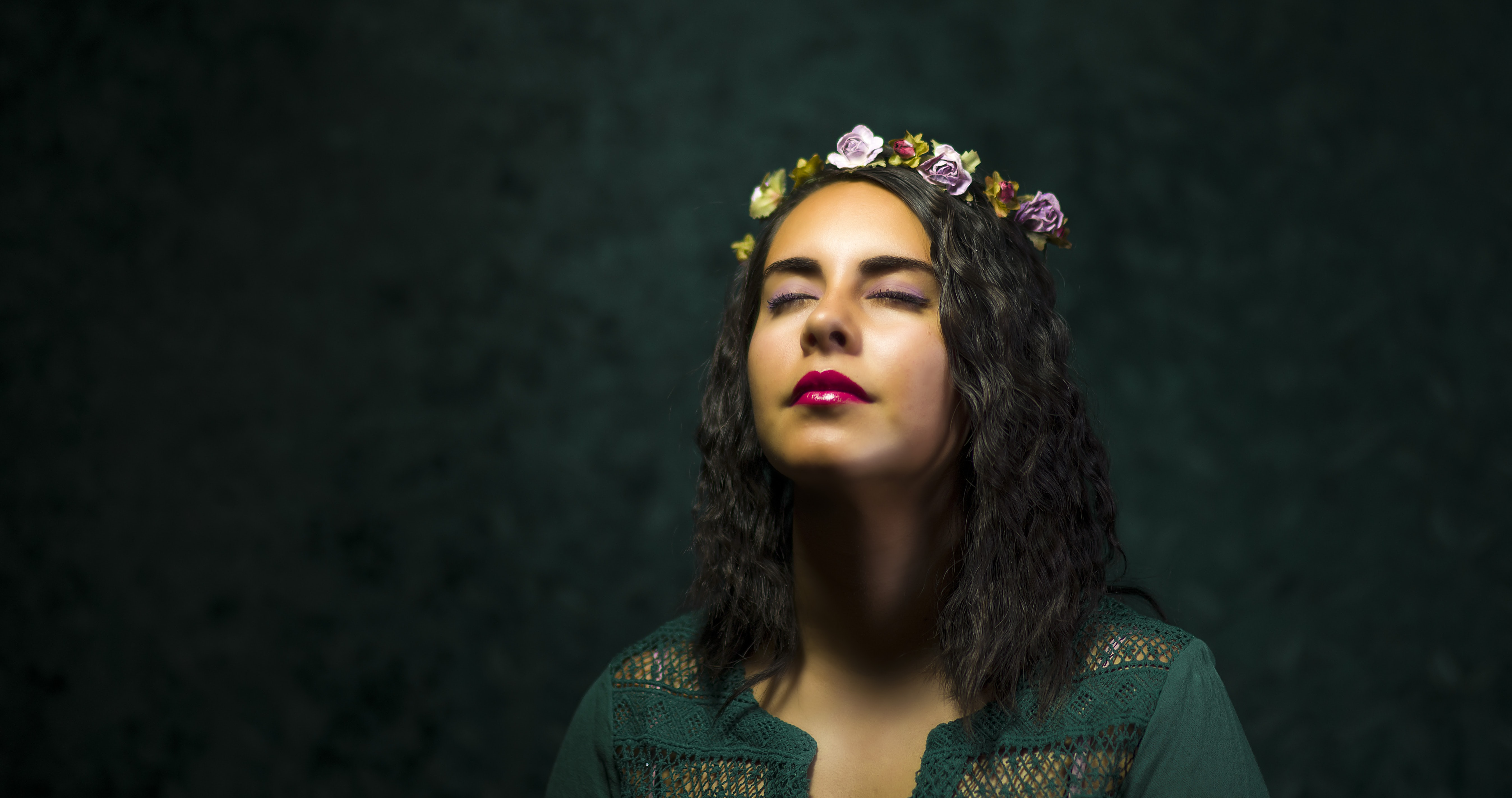 A dark-haired woman in a crown of flowers