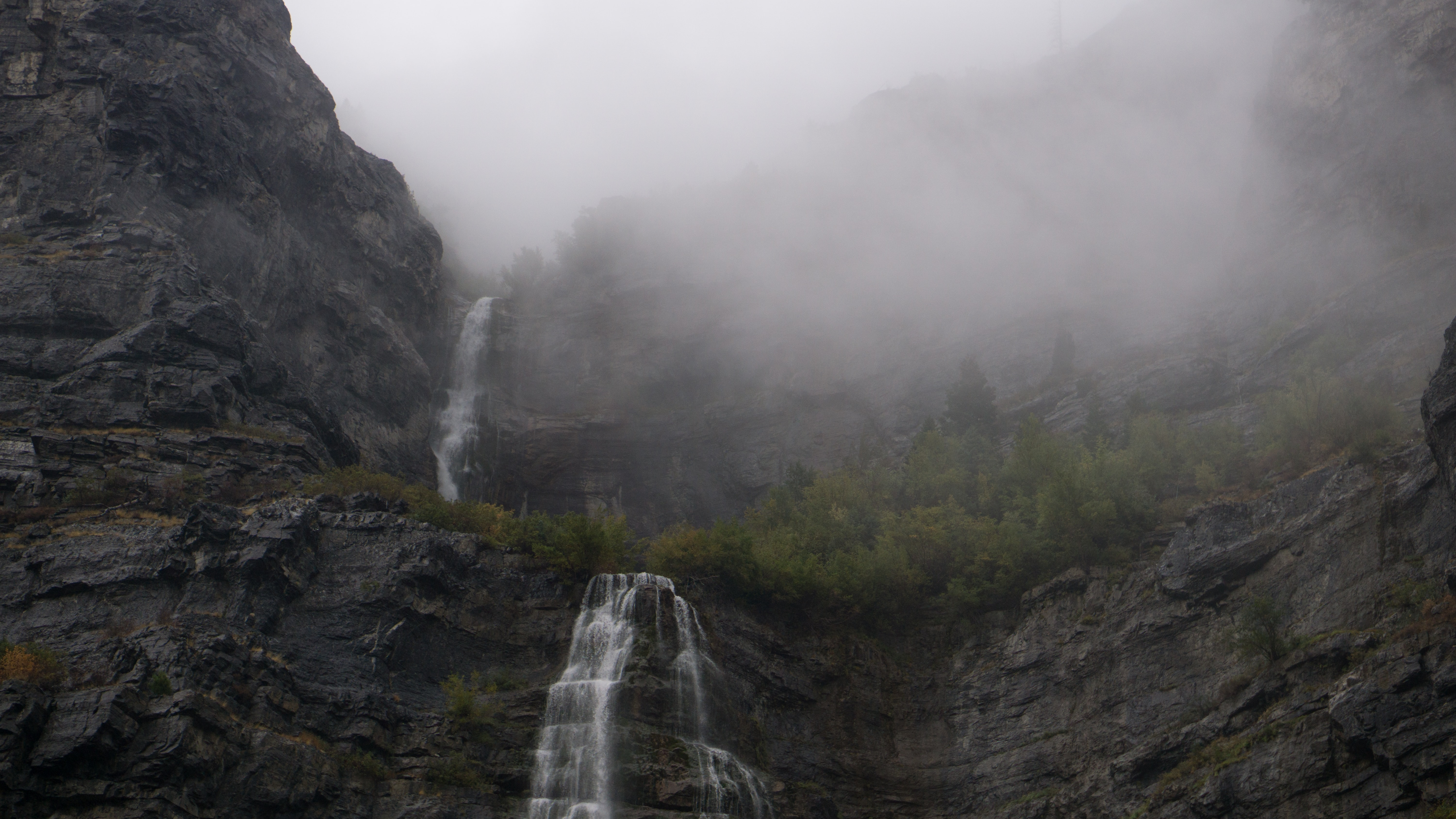 Two waterfalls cascading down a rock face on a foggy day
