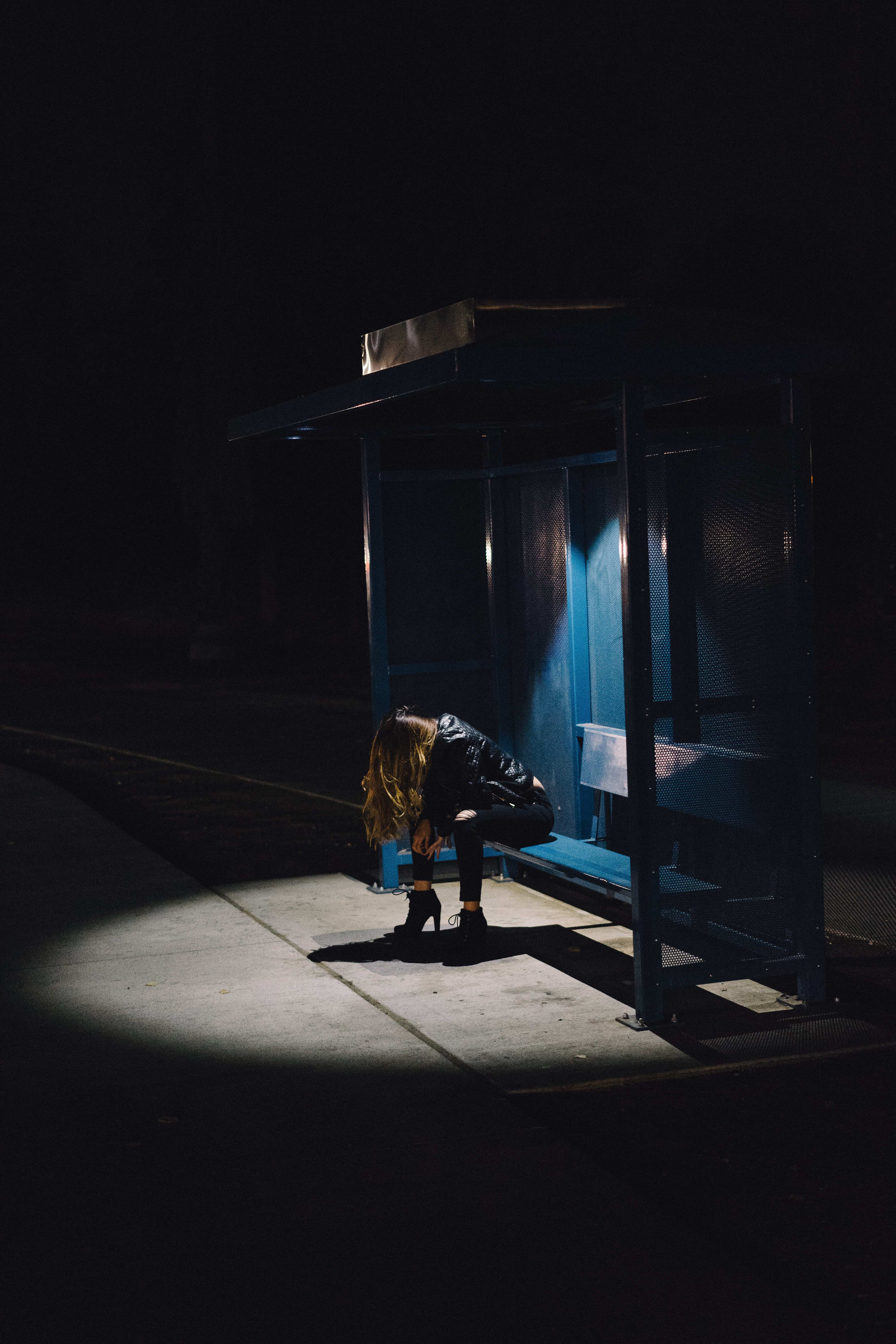 A woman with her head down being illuminated with the only lights of the bus stop.