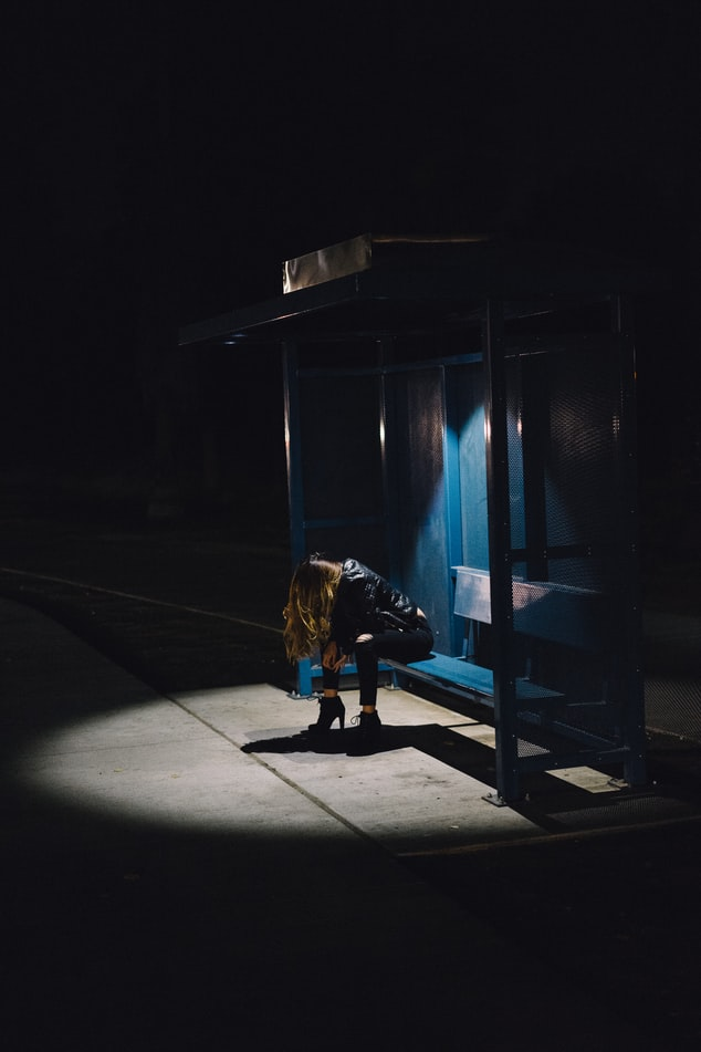 A woman sitting at a bus stop. It's dark all around here, there is a pool of light over her and she is bent over with her head in her hands. Her hair covers her entire face.