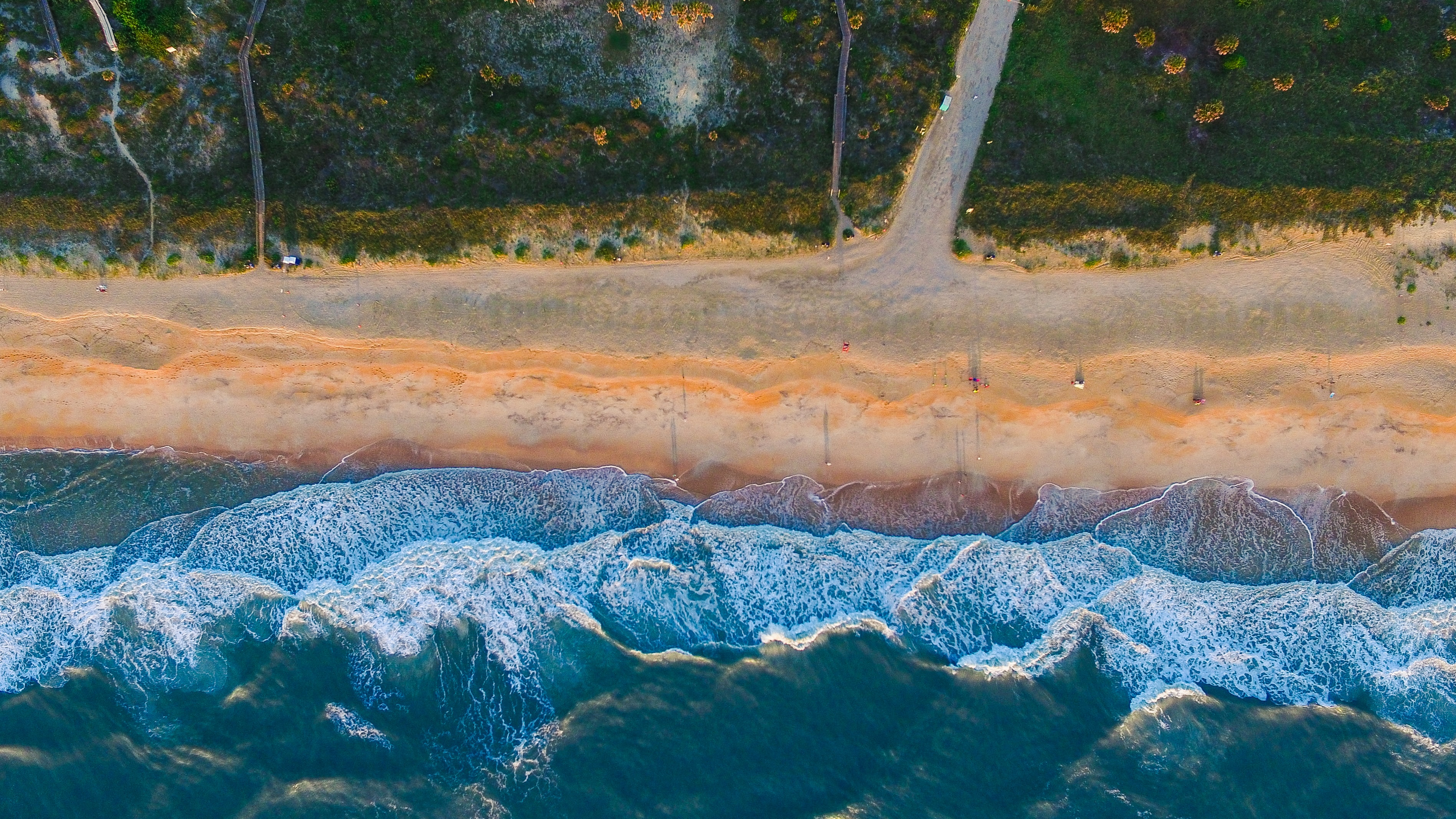 Drone view of the ocean washing on a sand shore by the forest