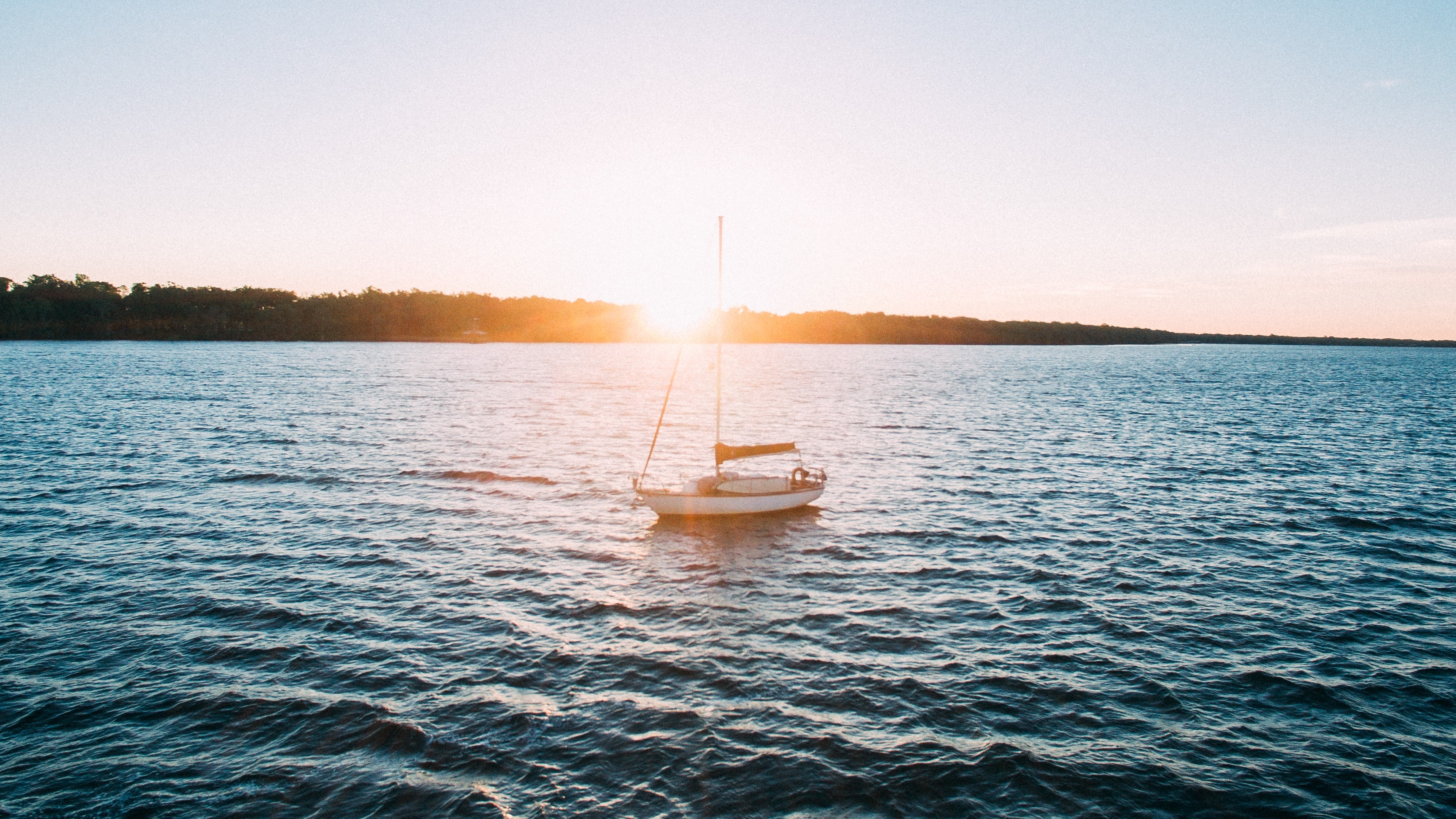 Sail boat on the ocean as sun rises above the forrest horizon