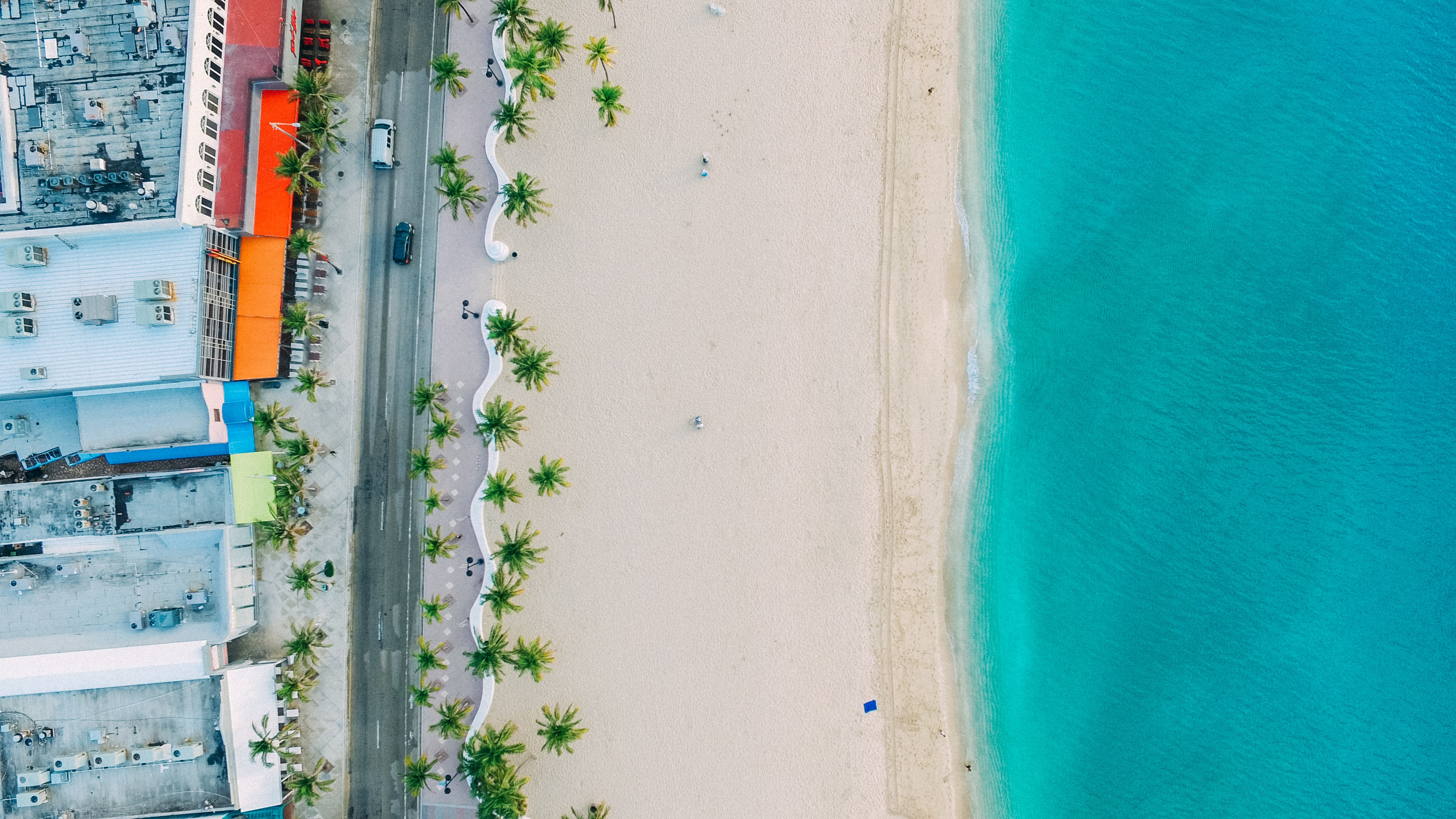 An aerial shot of an empty white sand beach and clear turquoise sea