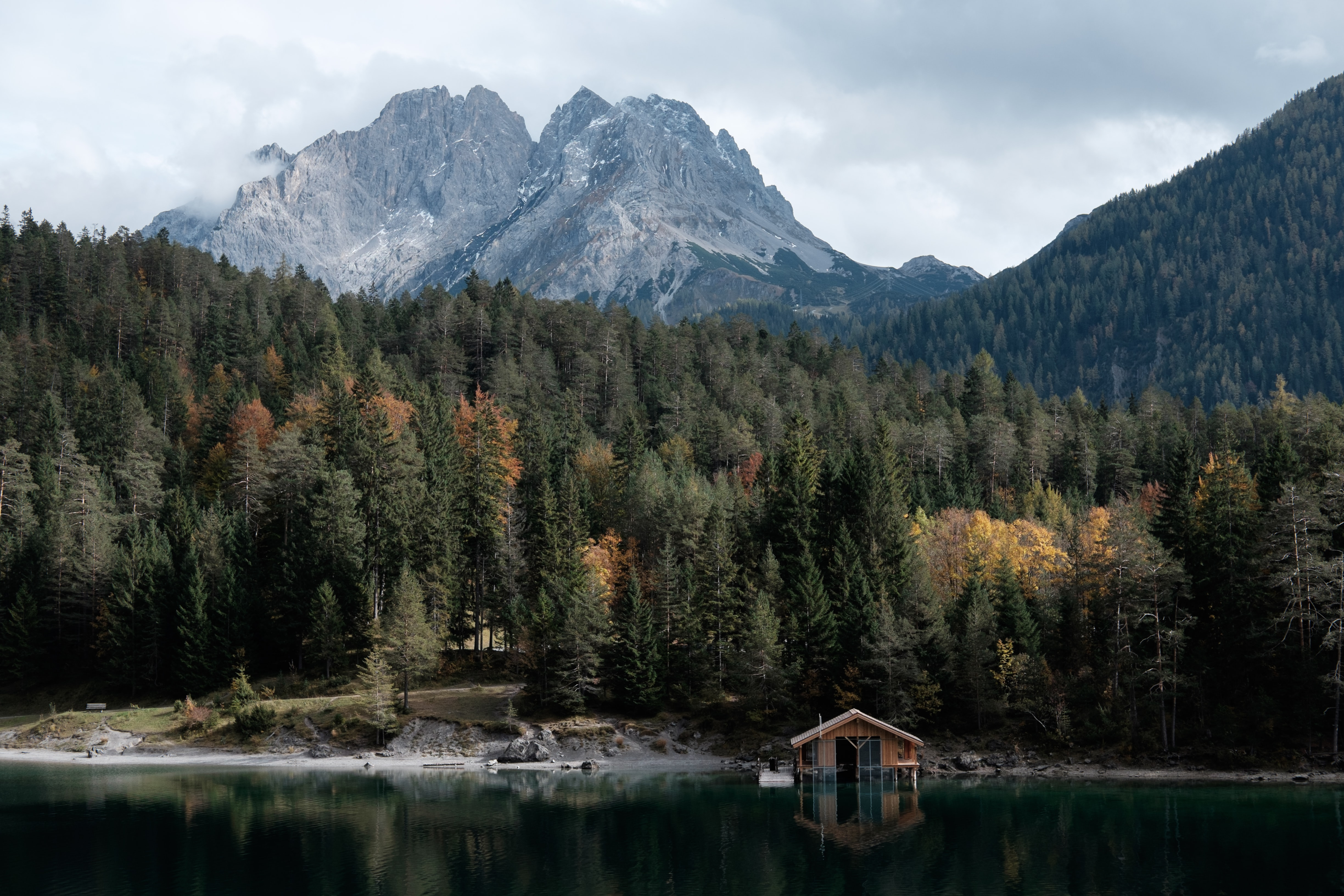 A boathouse on a quiet lake with imposing mountains on the horizon