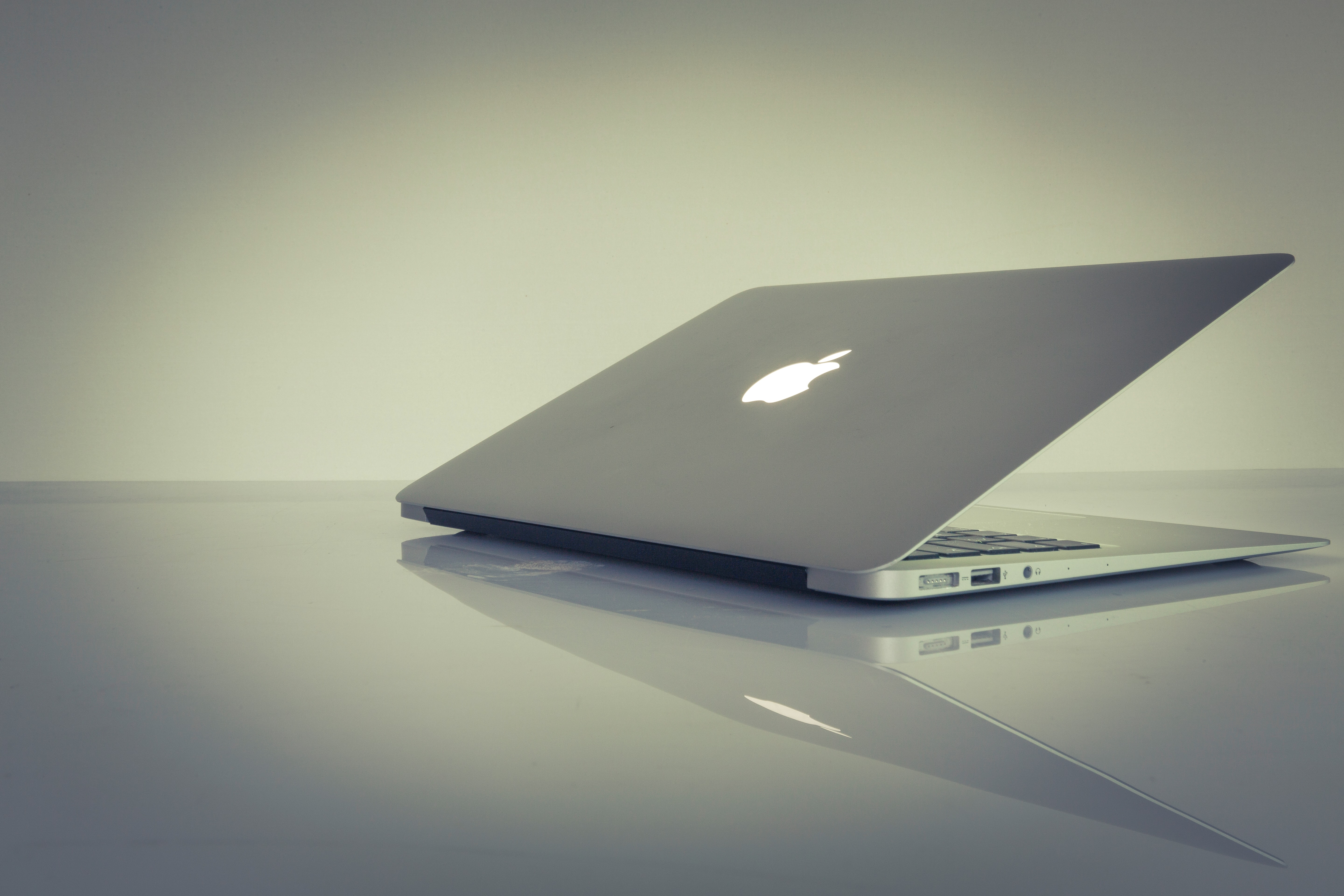 A half-closed MacBook on a reflective surface