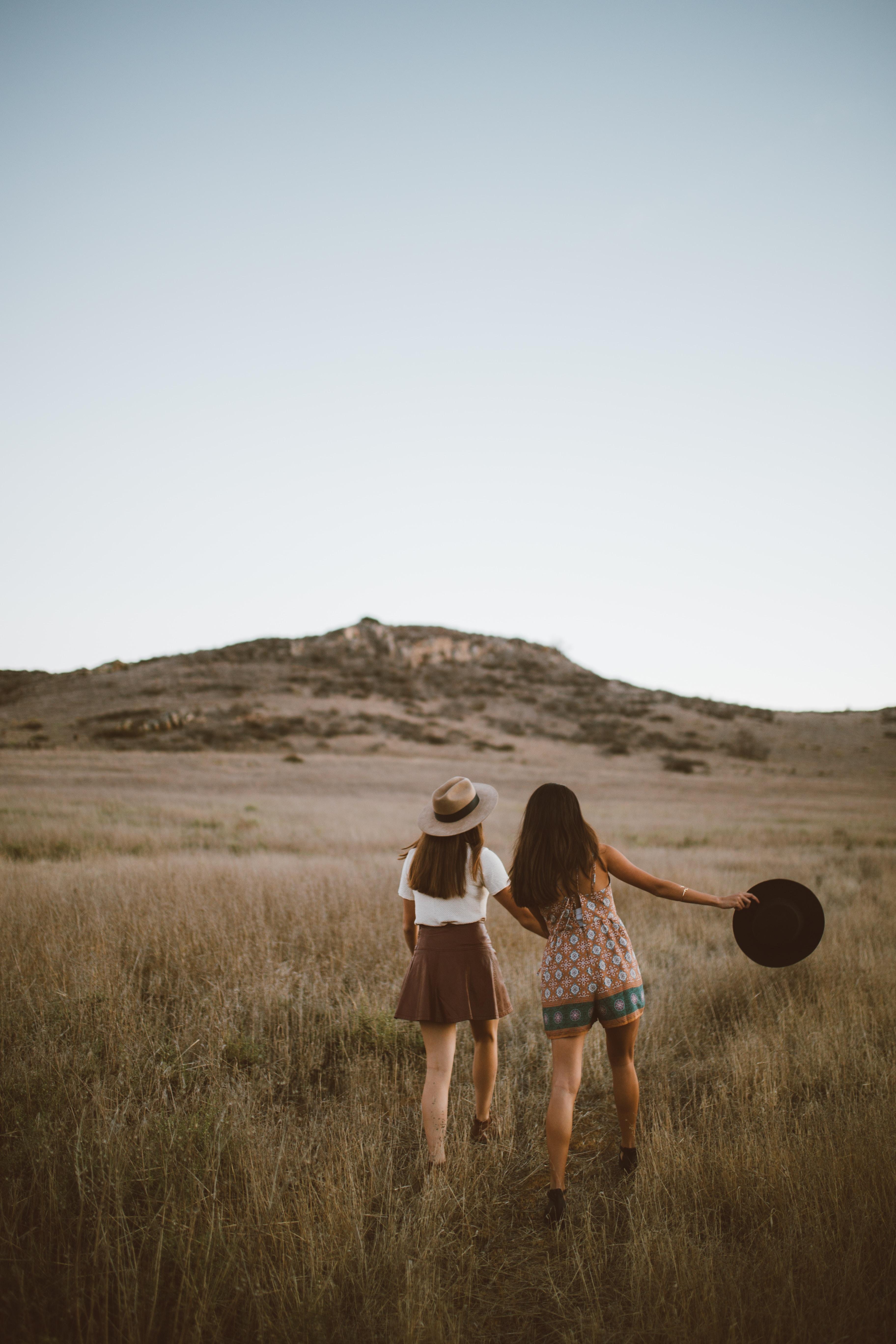 two women walking around near mountain at daytime