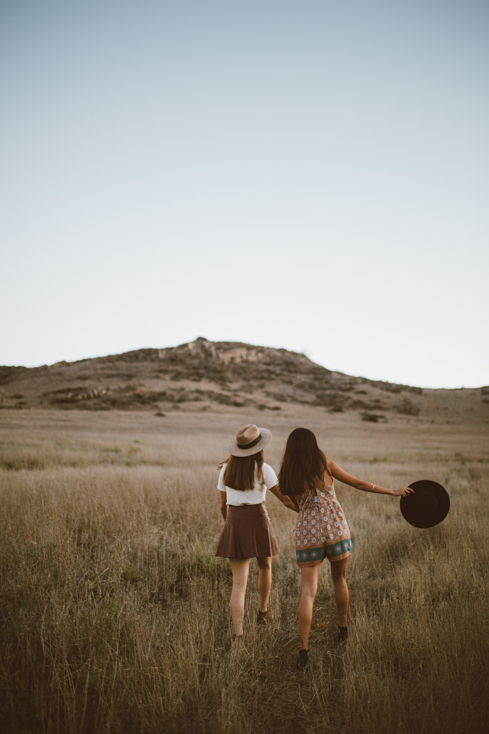 two women walking around near mountain at daytime