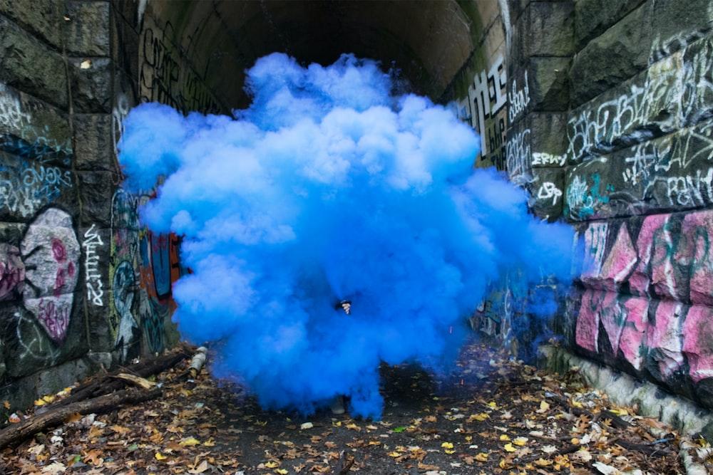 photo of blue smoke beside walls with graffiti