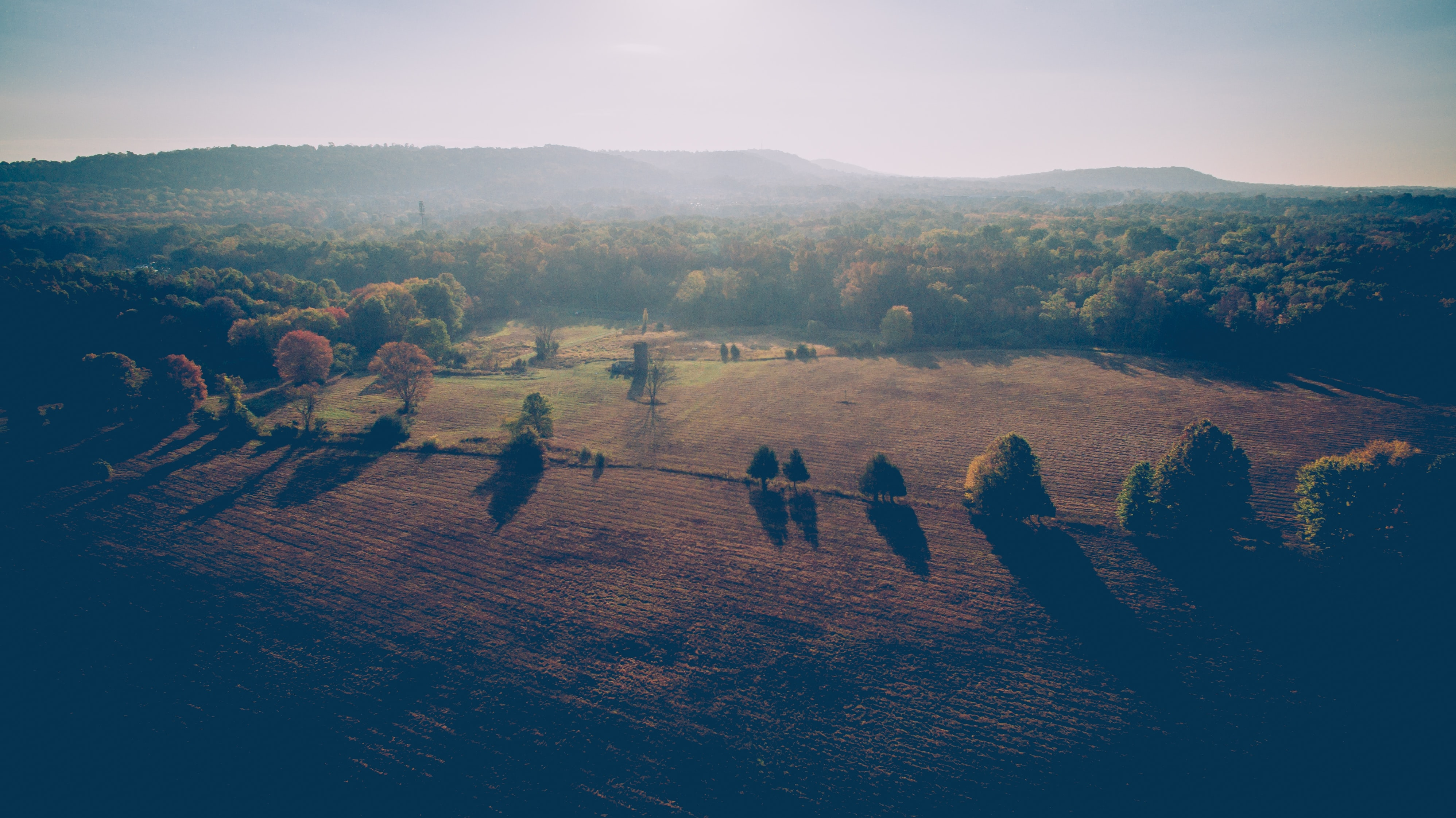 A hazy shot of autumn forests around plowed fields in Somerset County