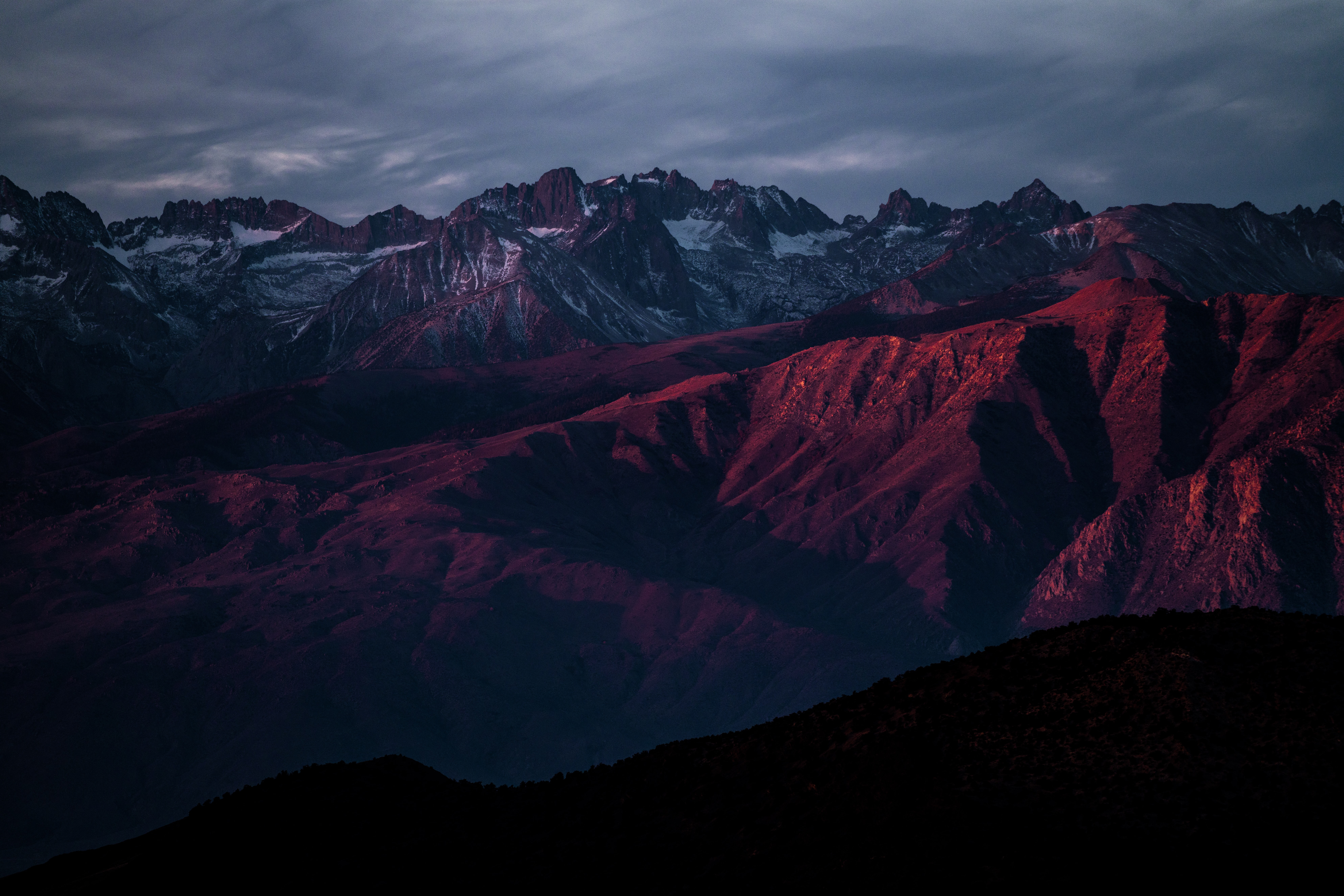 A red-hued shot of a mountainous landscape with numerous snow-capped peaks