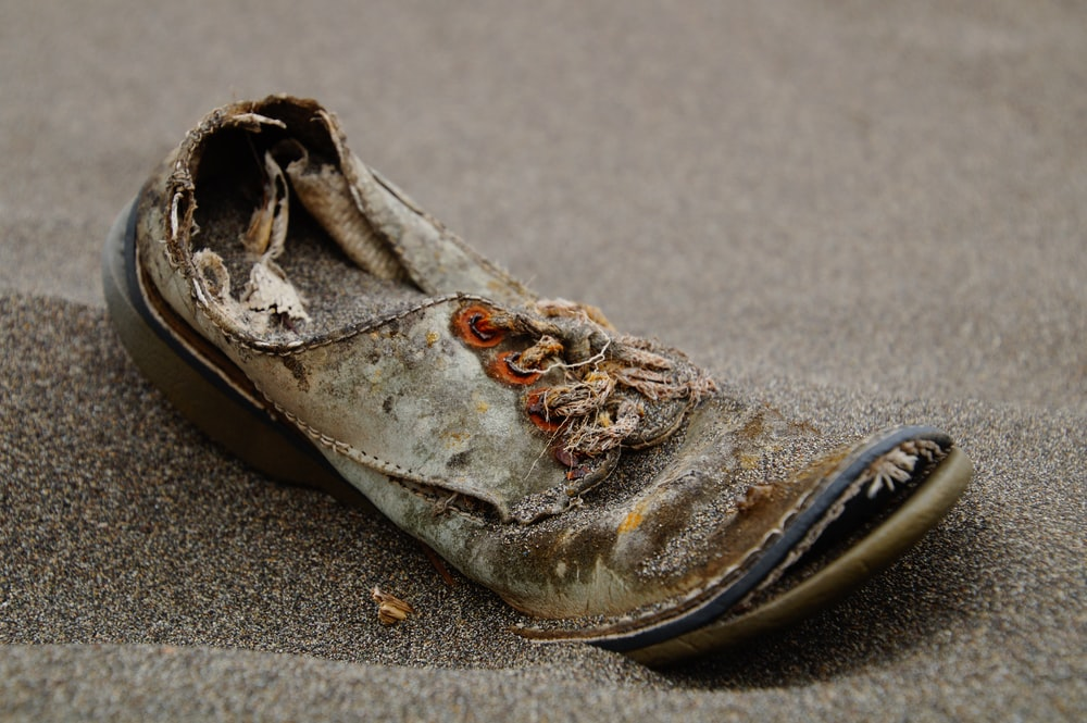 unpaired brown and black shoe on sand