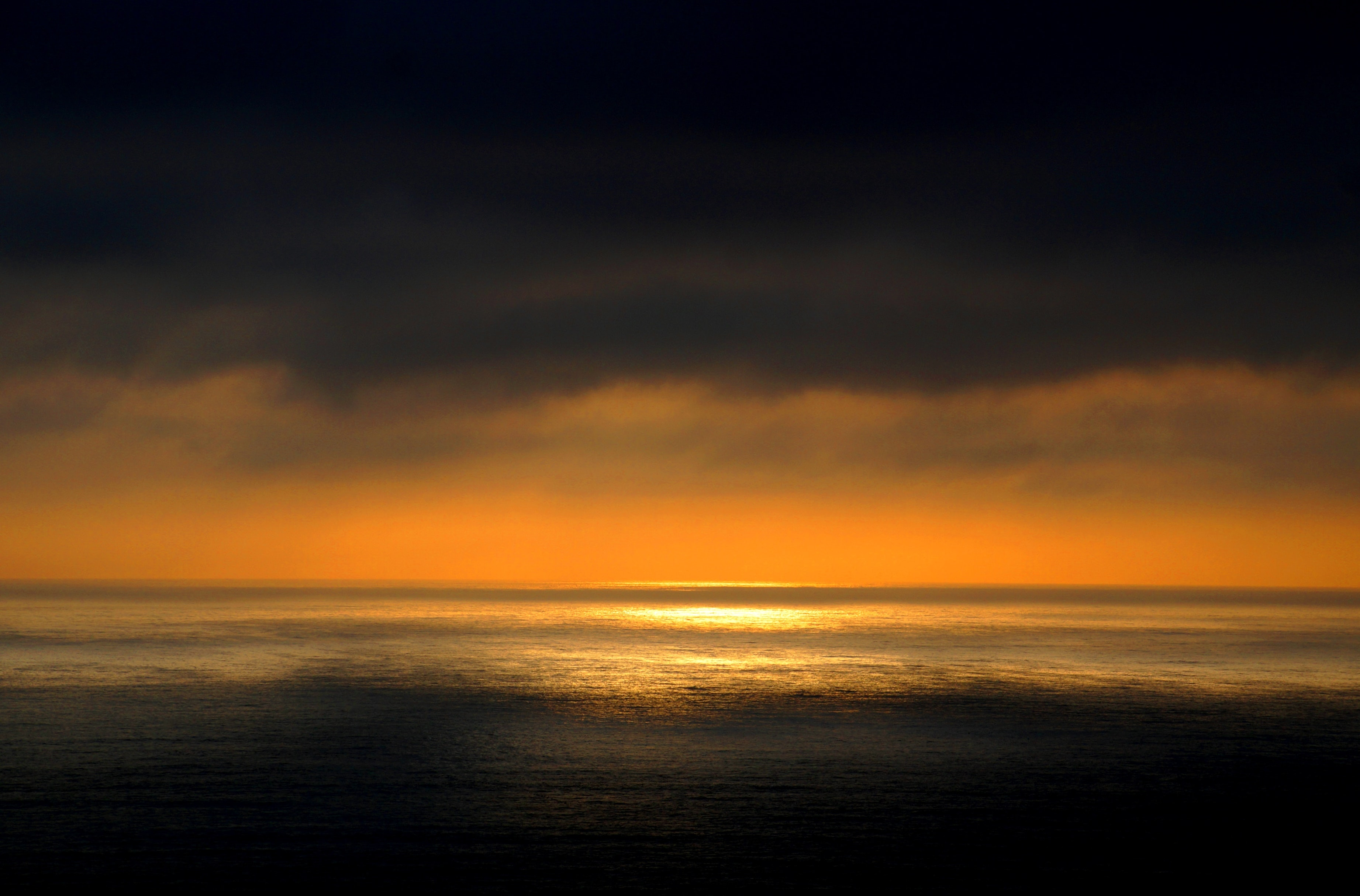 A dark and moody sunset over the ocean with yellow and orange rays on the horizon in Chile.