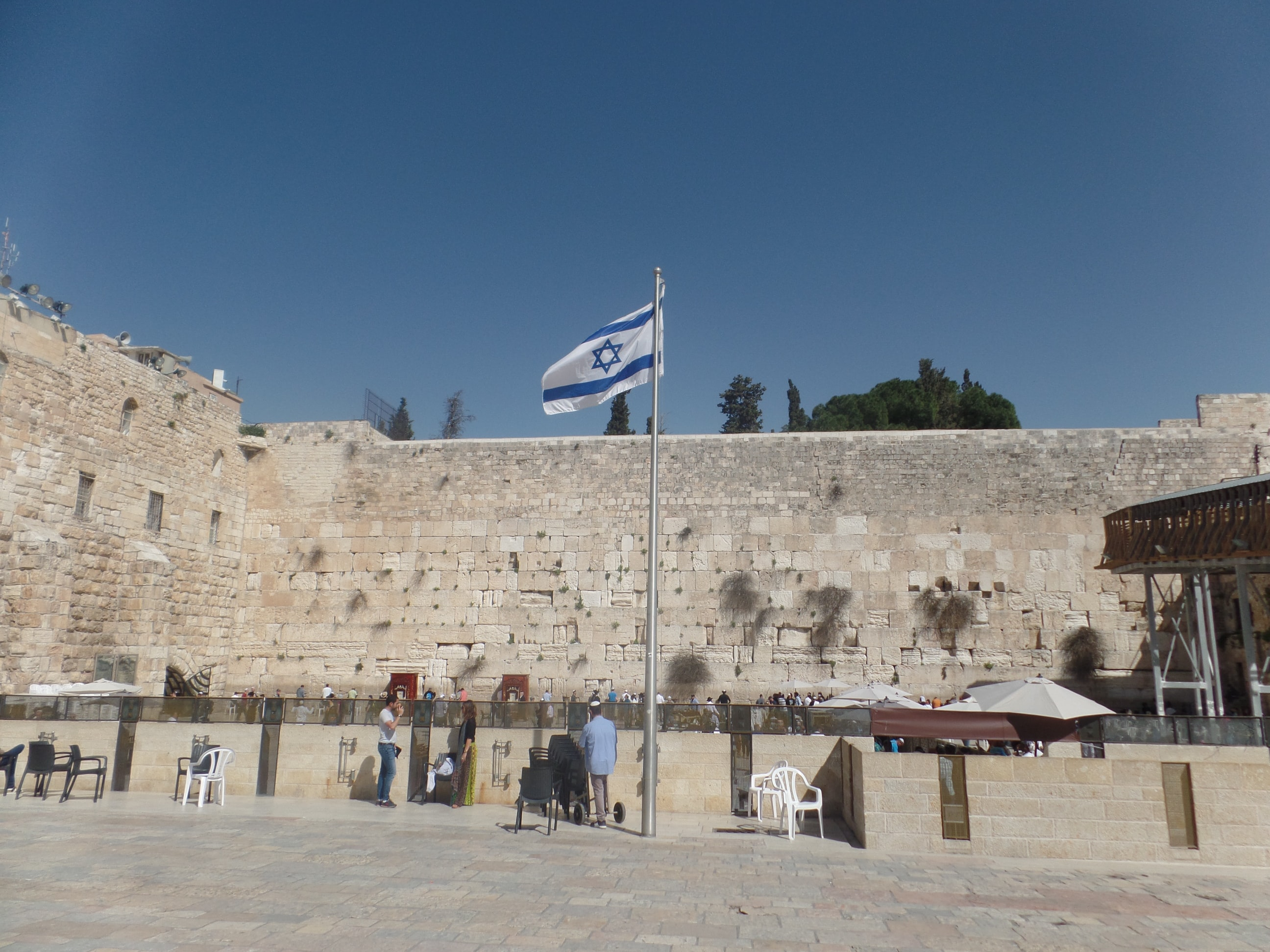 People talking to each other in a gathering spot in Israel, with the nation's flag raised high.