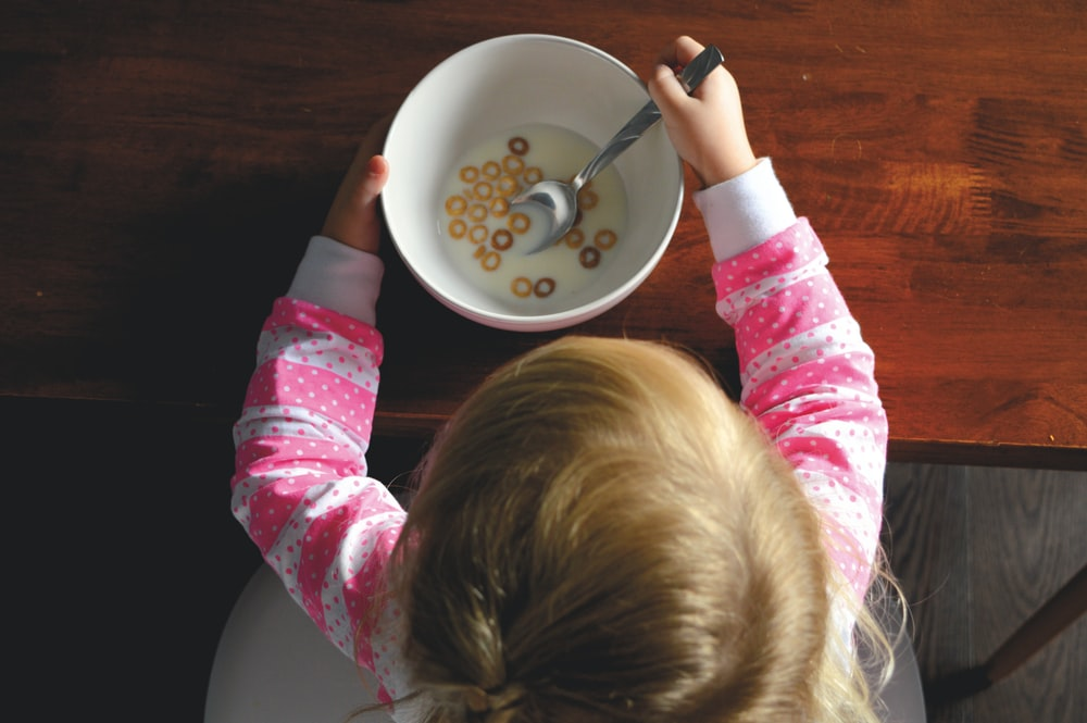girl eating cereal in white ceramic bowl on table