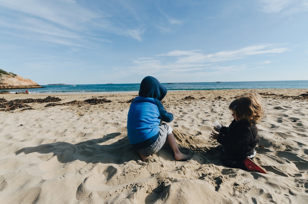 two kid in sand during daytime