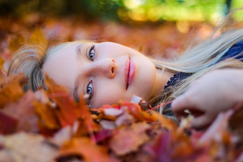 woman wearing blue top lying on dried maple leaves during daytime photography