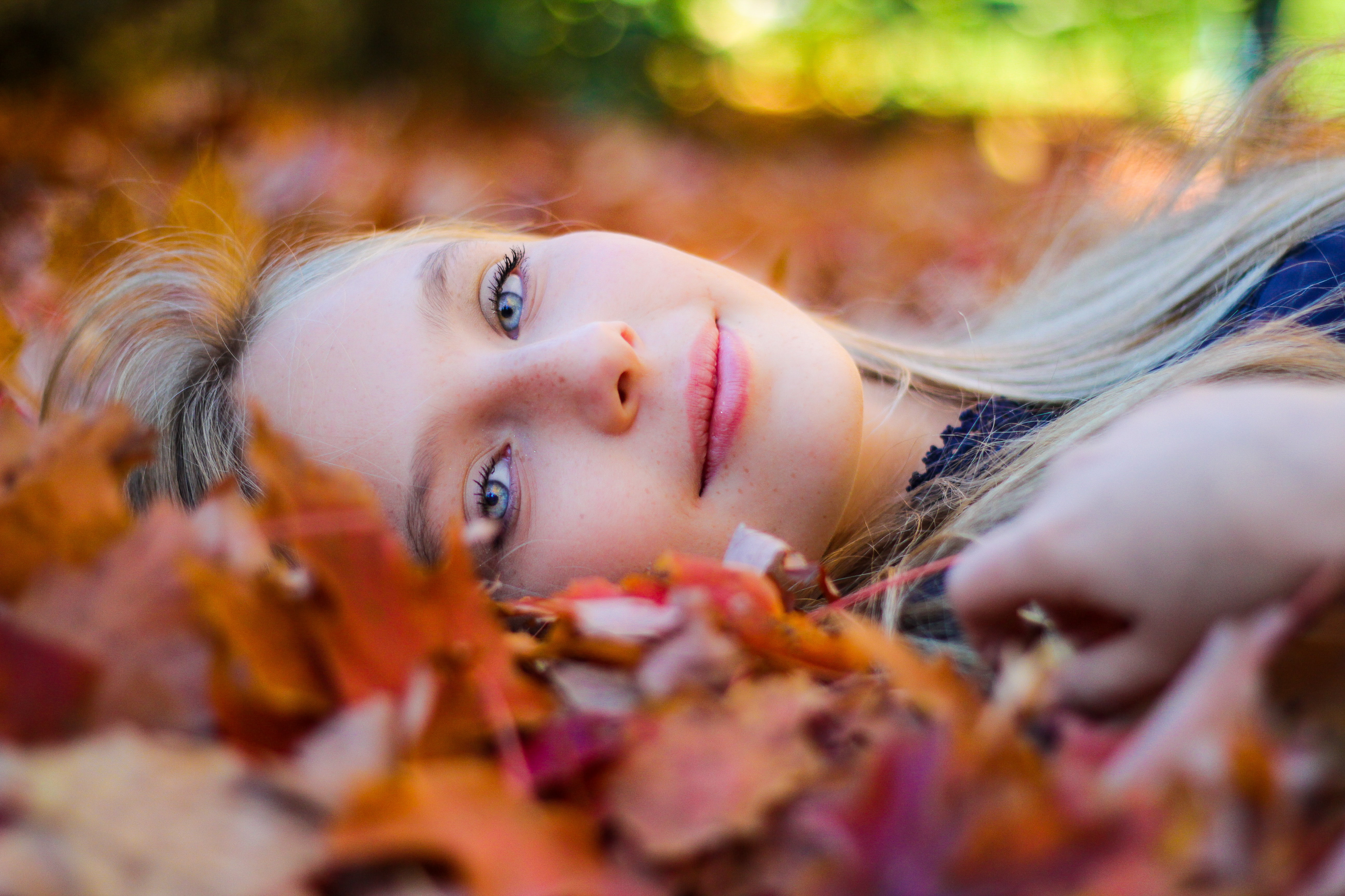 A smiling blonde woman lying in fallen leaves at the Arnold Arboretum of Harvard University
