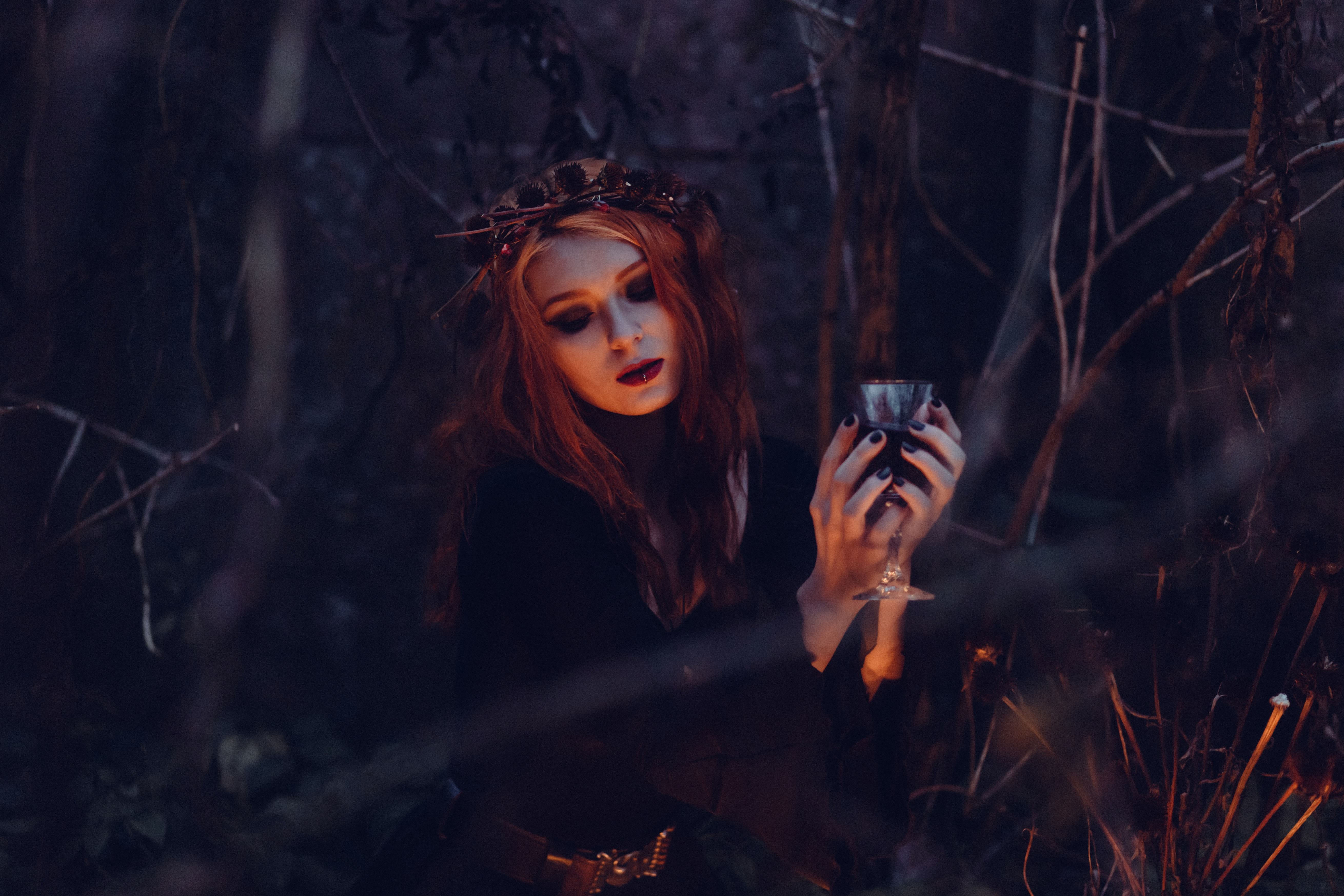 A girl in the woods holding a glass of wine on Halloween.