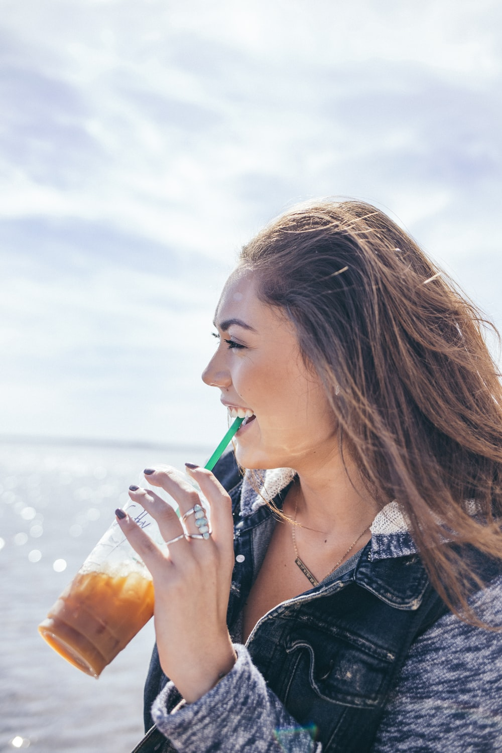 woman wearing black and grey jacket holding glass cup while drinking near body of water during daytime