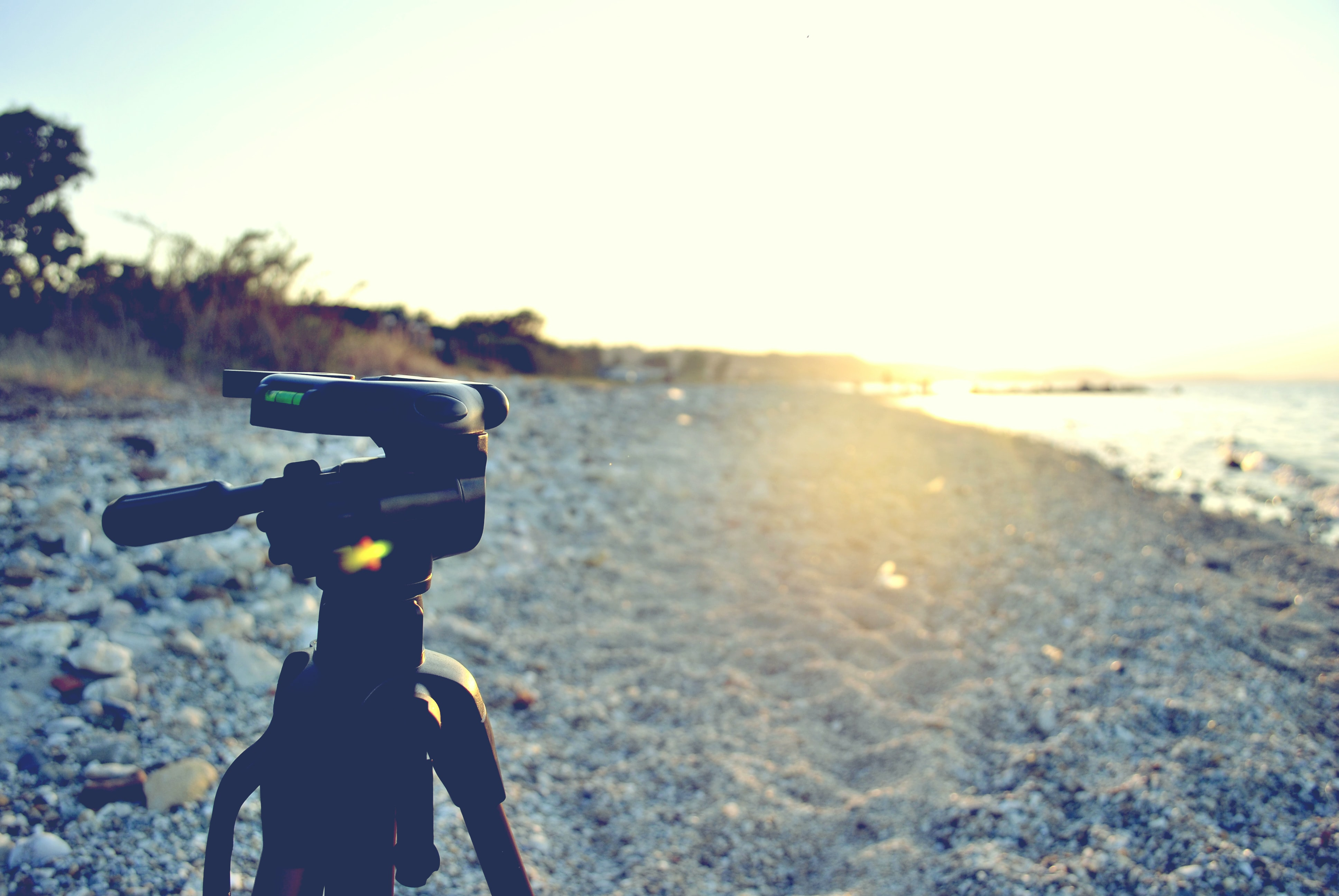 Camera tripod on a rock pebble beach at sunset in Halkidiki