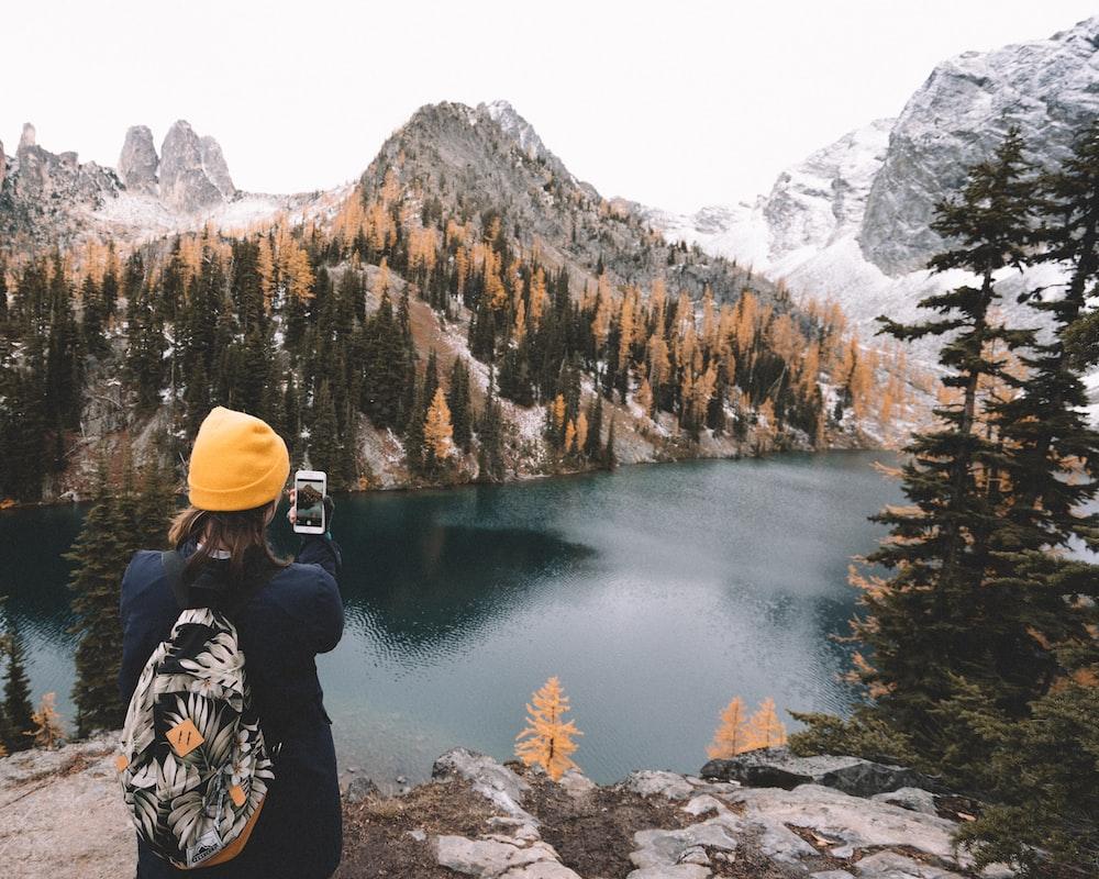 woman taking photo of lake during daytime