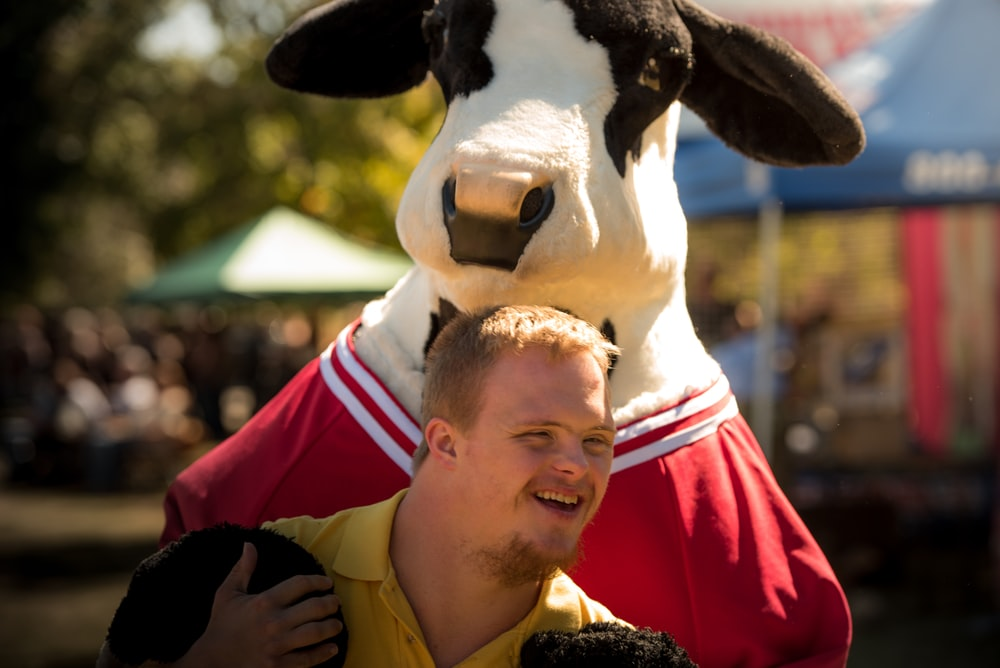 smiling man wearing yellow polo shirt standing near cattle cosplay
