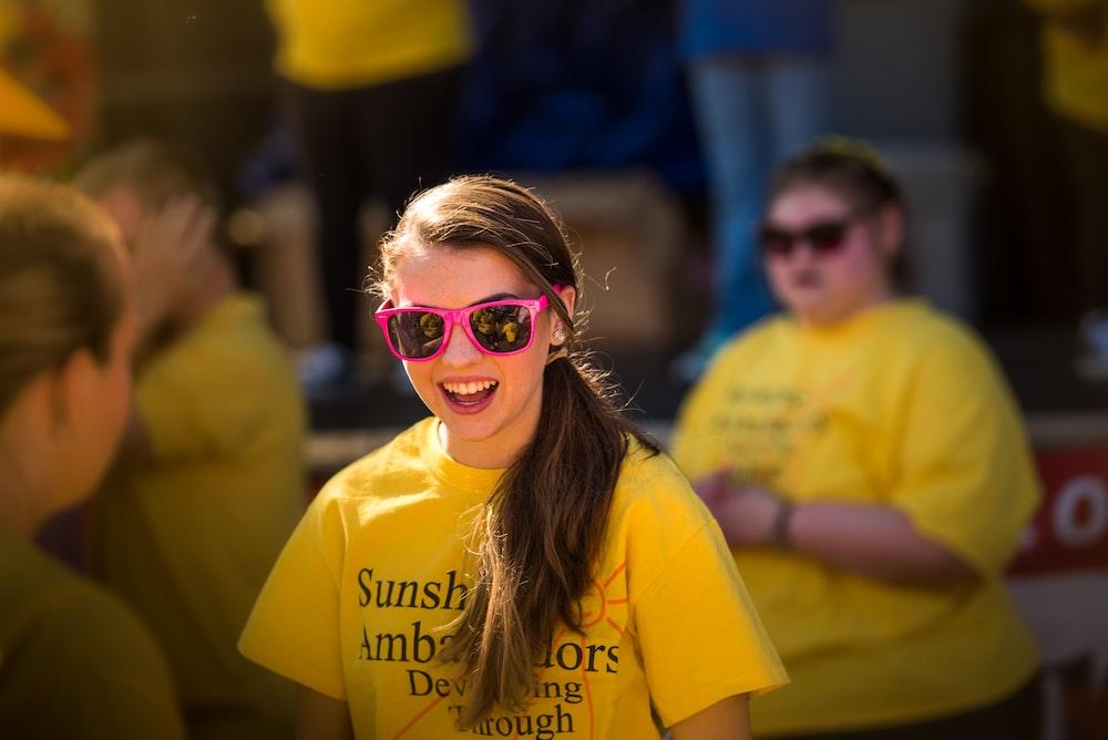 smiling girl wearing pink framed sunglasses