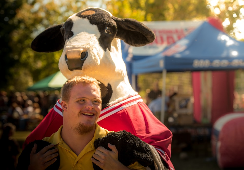 men near cow mascot