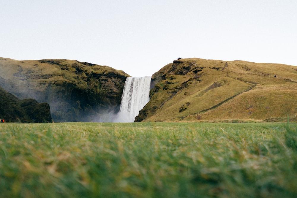 green grass field near waterfalls
