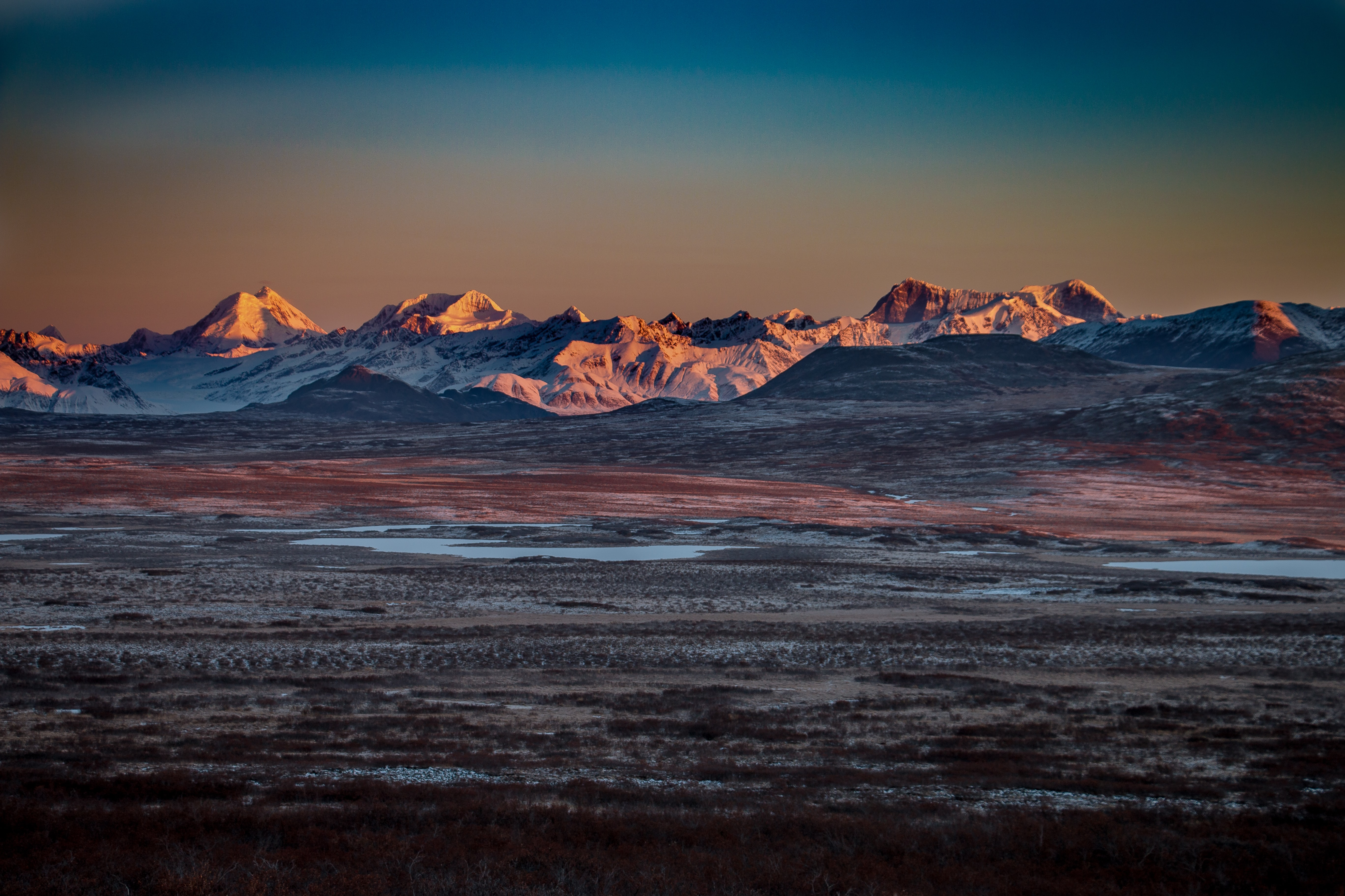 Frozen tundra near the mountains during sunset
