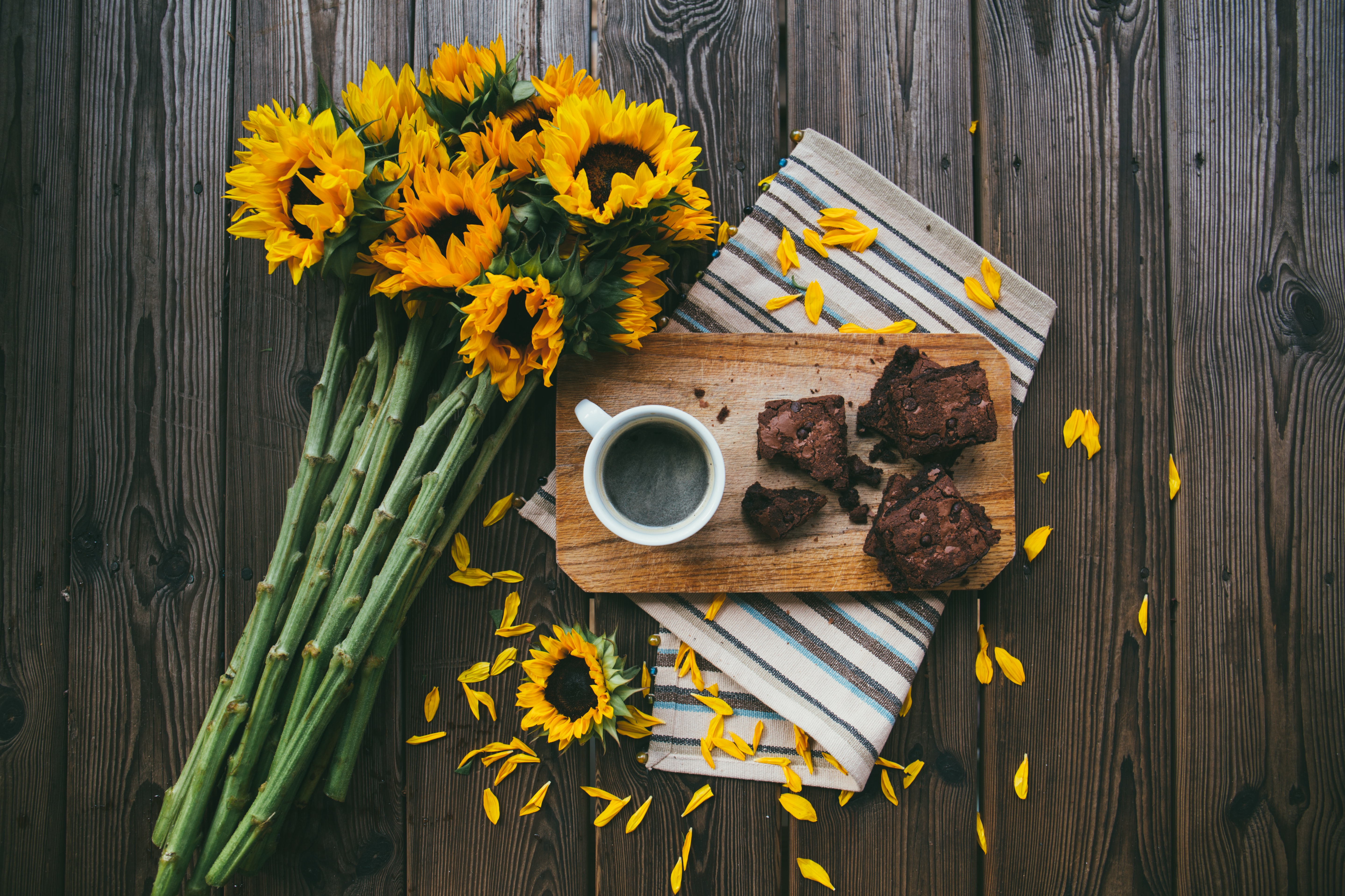 A bouquet of sunflowers, striped placemat, wooden board, cup of coffee, and brownies on a table