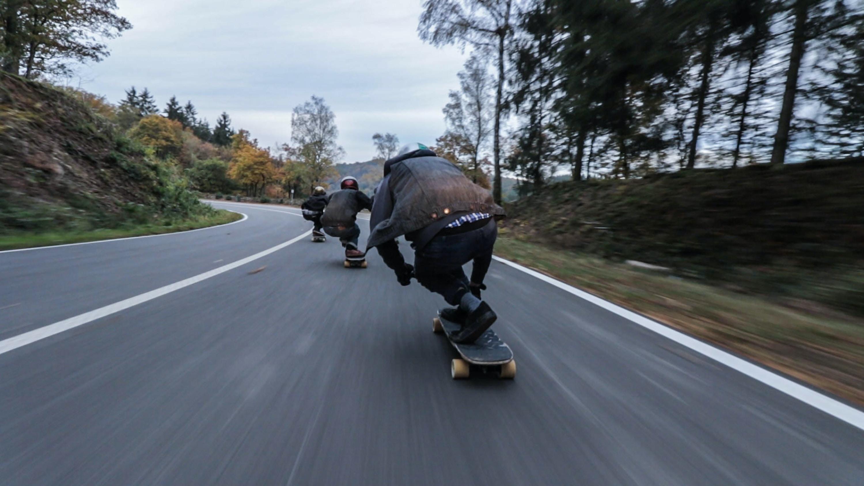 Three skateboarders speeding on an asphalt road
