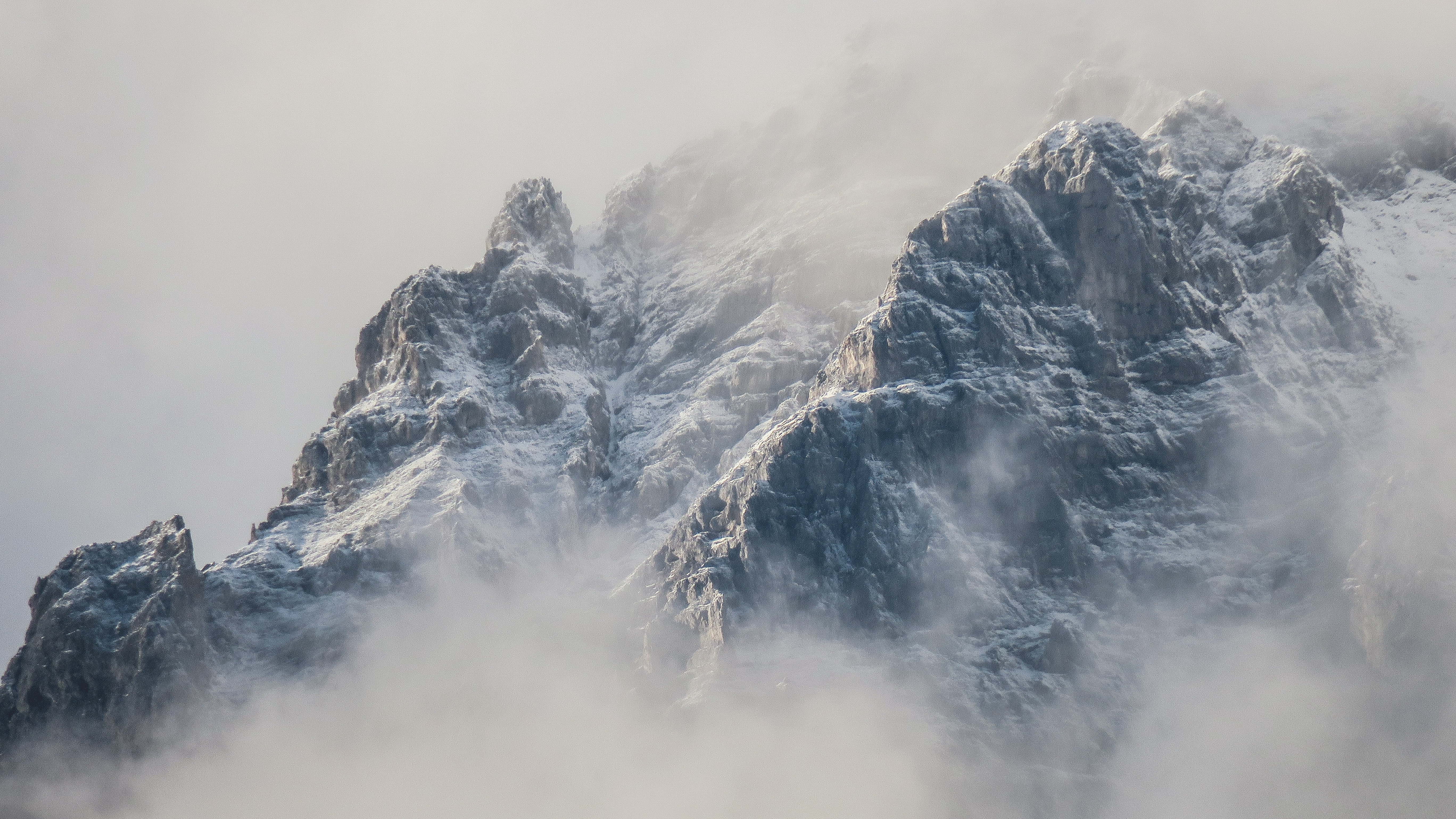 Misty alps and snowy mountains on a foggy day in Innsbruck