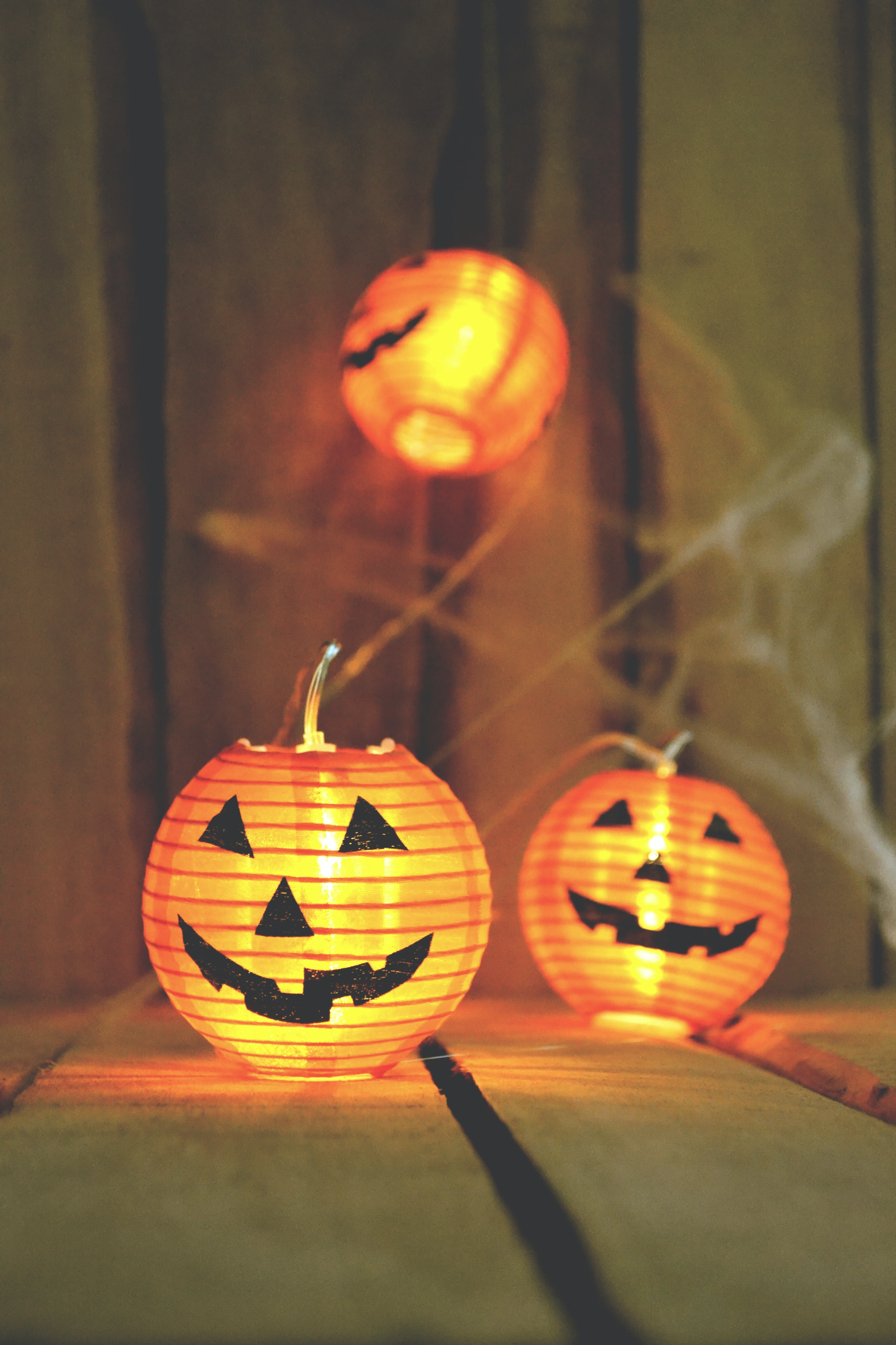three jack-o-lantern lamps on beige wooden board