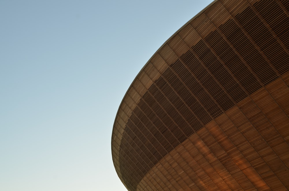 The saucer-like facade of a sports arena against blue sky