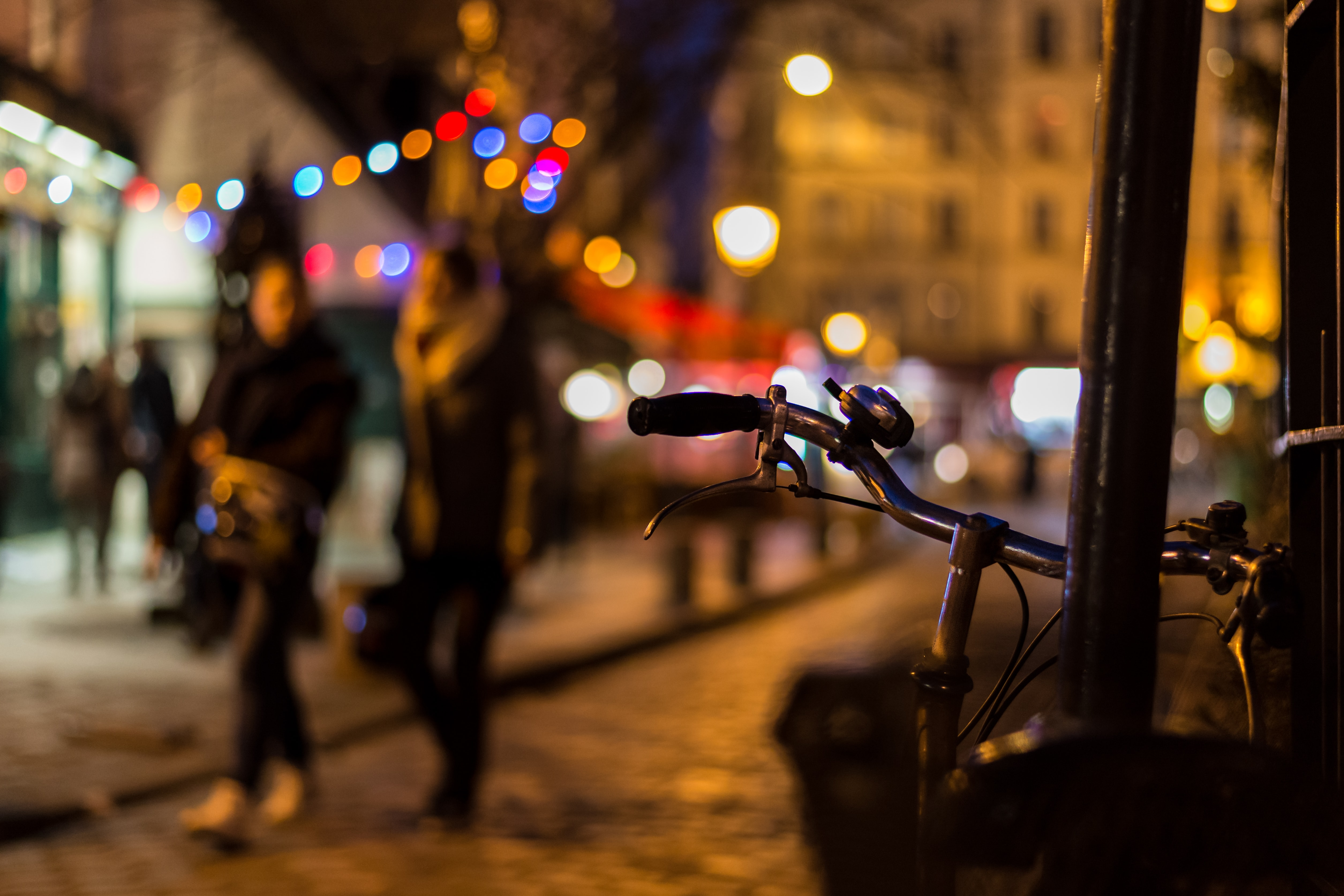 A bike and bell in focus with blurred people and a bokeh effect in the background