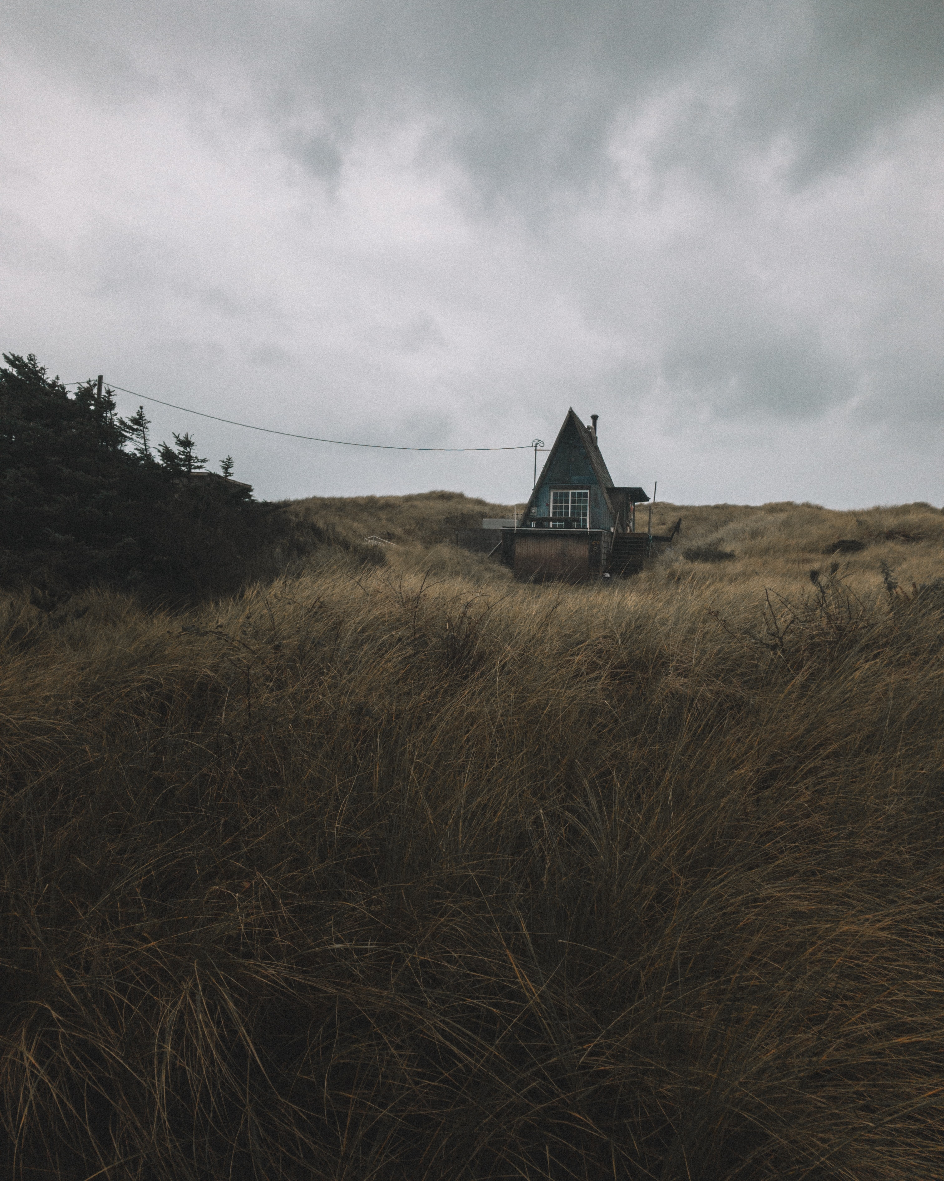 A small hut in a grassy field on a cloudy day