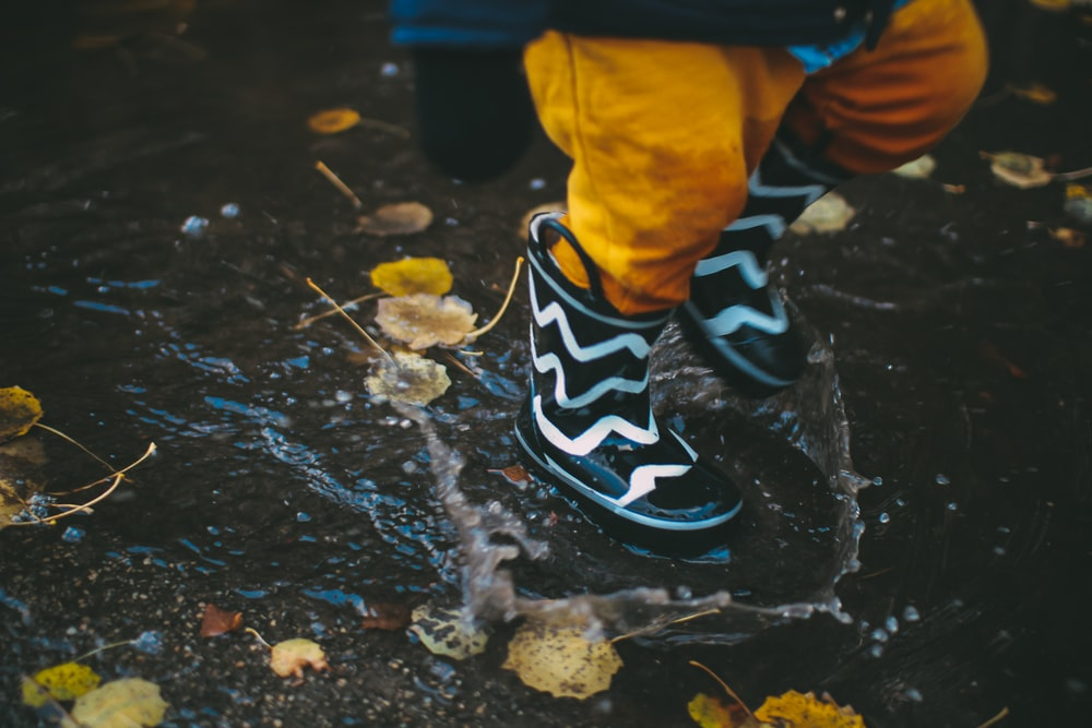 toddler wearing black and white rain boots standing on body of water