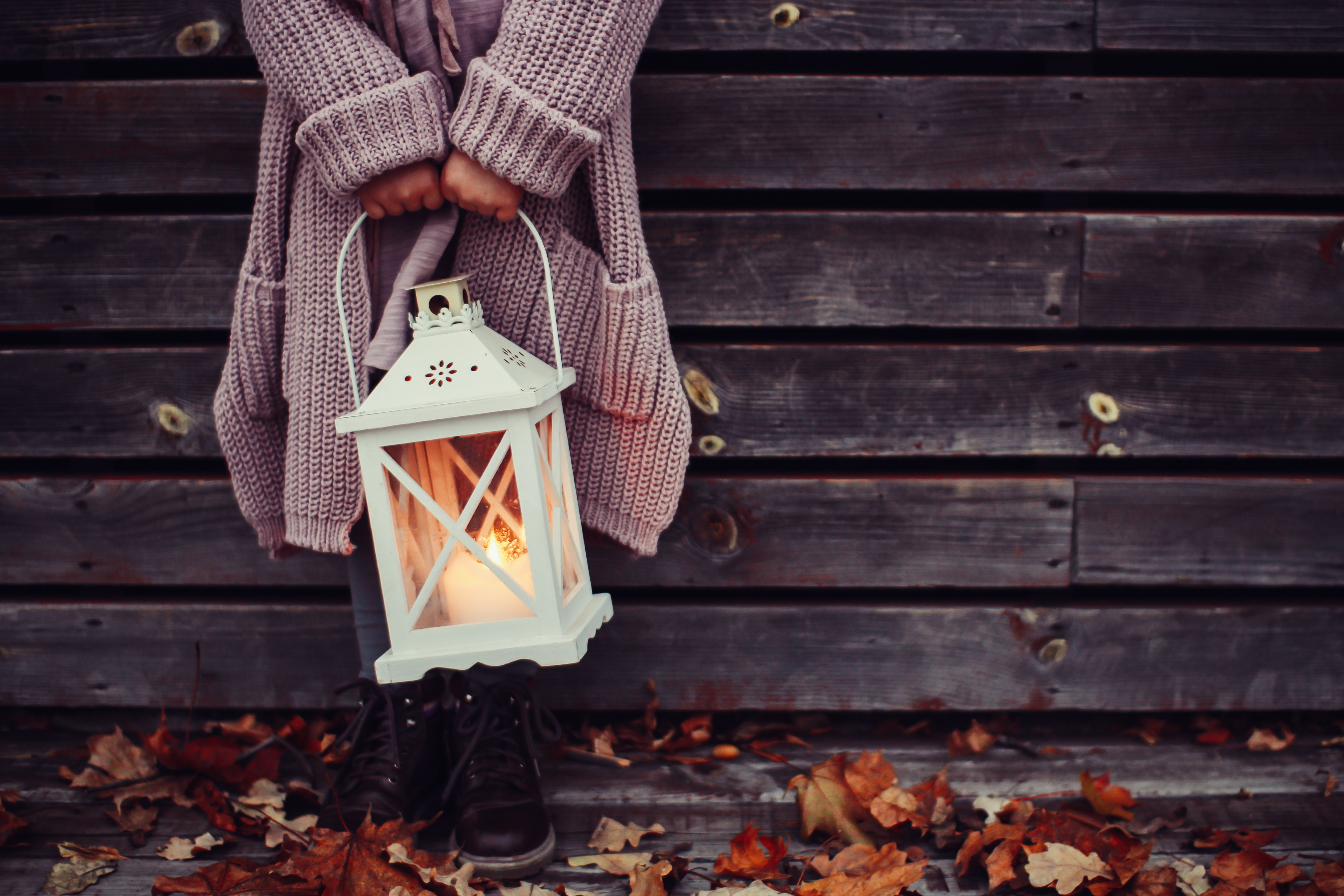 A child holding a lantern with a candle near a wooden wall in the autumn