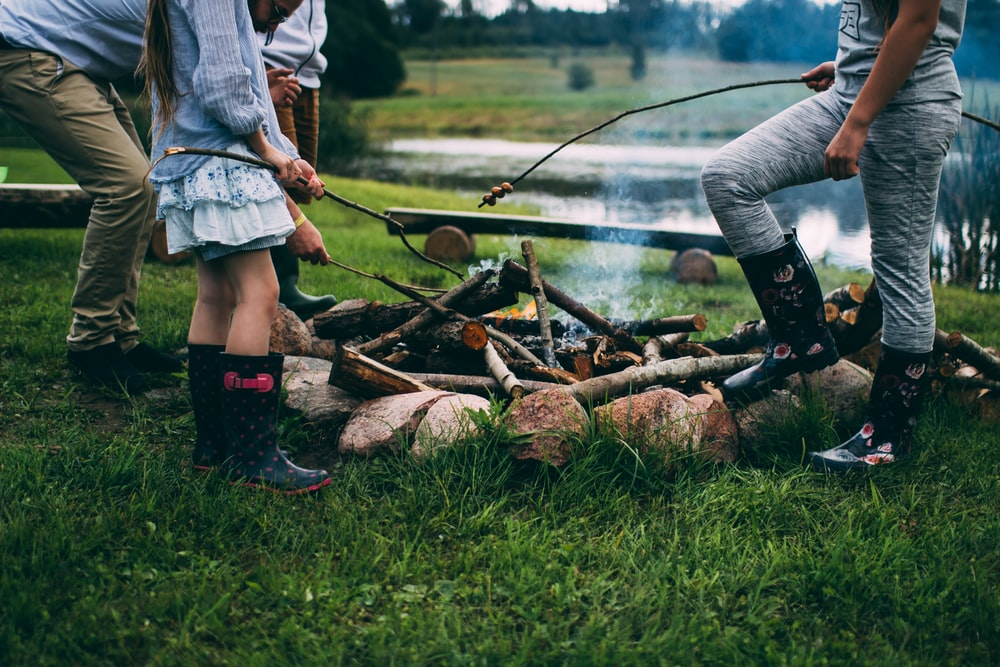A family standing around a campfire, wearing wellies, roasting marshmallows in Ērgļi
