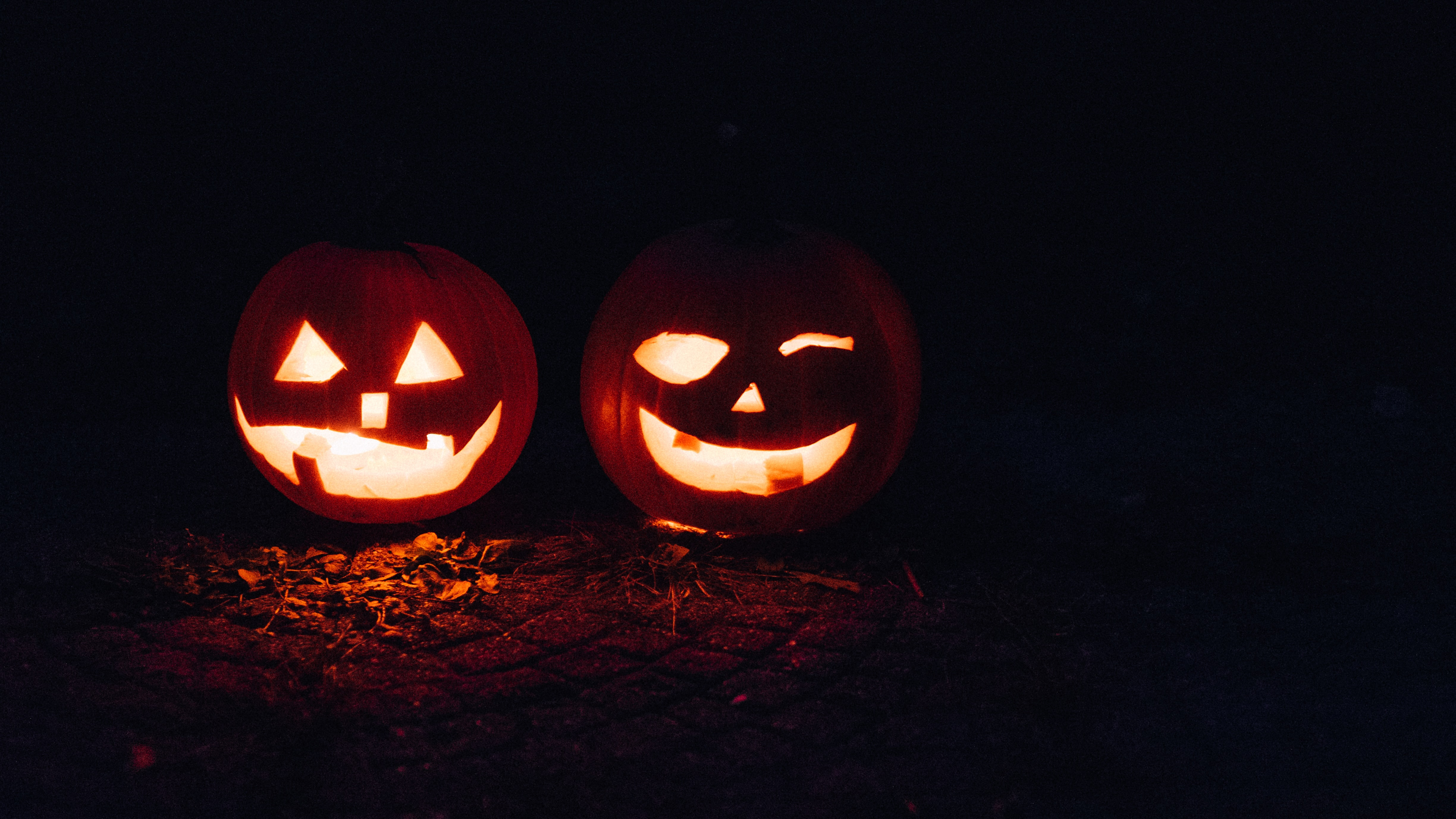 A pumpkin carved into a smiley face with shapes as the eyes and nose during Halloween as a lantern