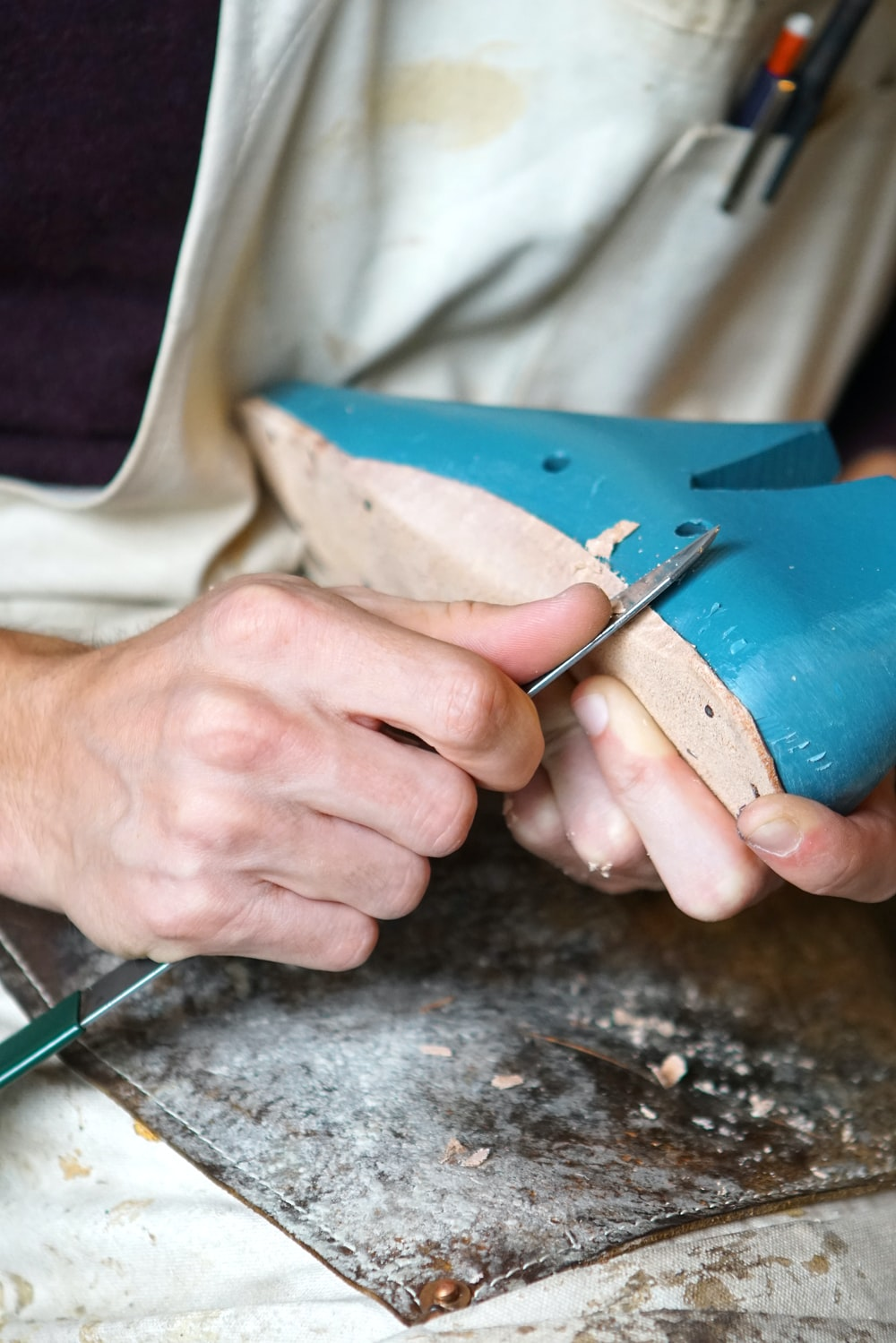 person carving blue footwear
