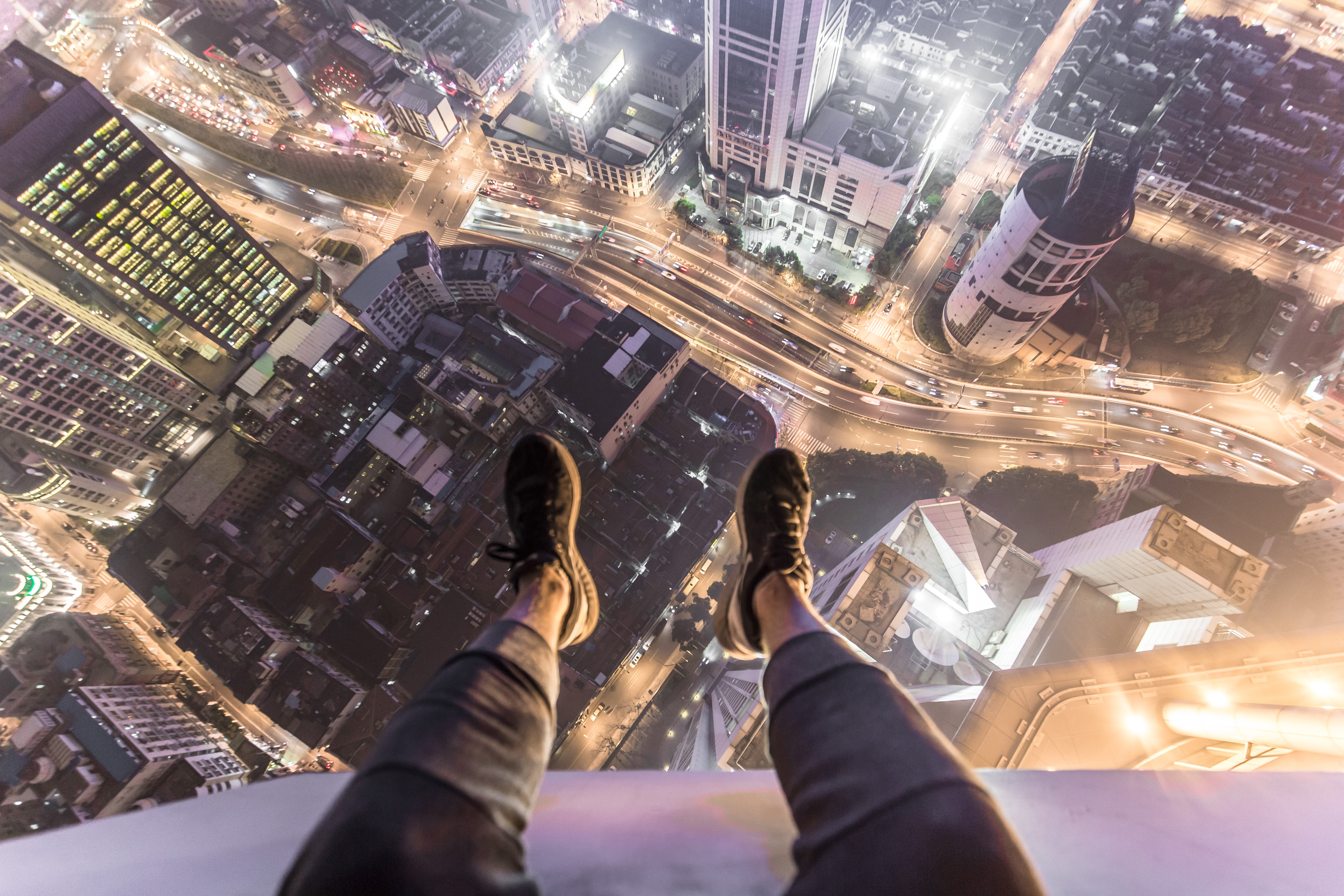 A person sitting on top of a skyscraper and dangling their legs over the edge.