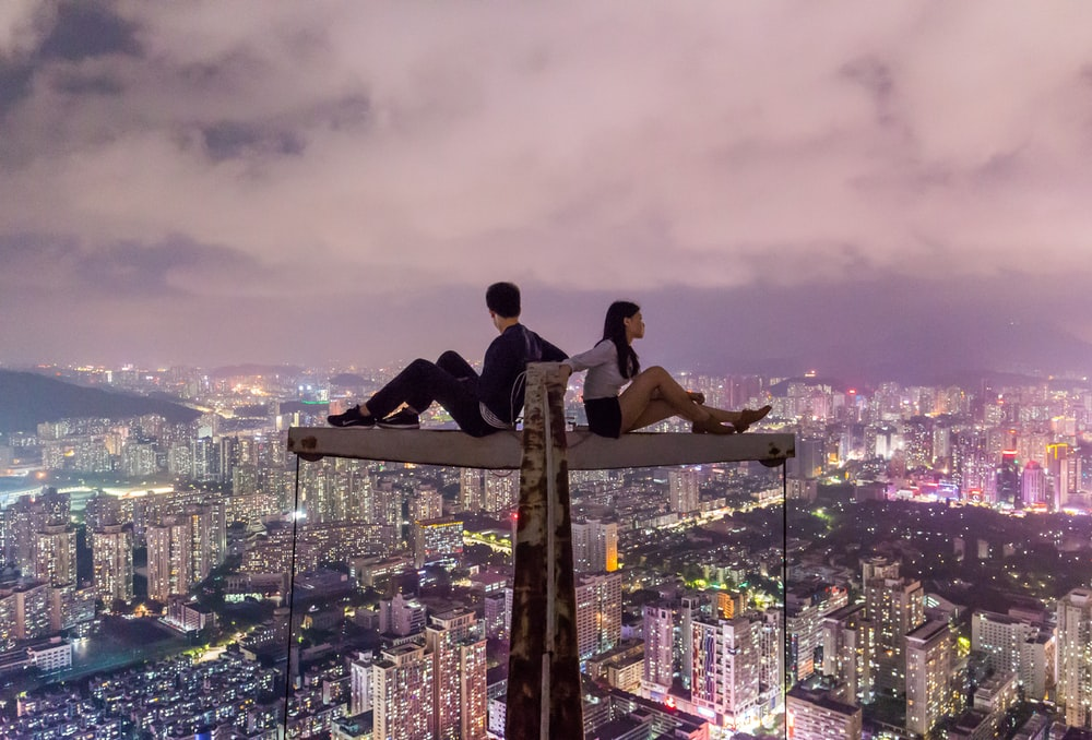 man and woman sitting on metal on top of high rise building