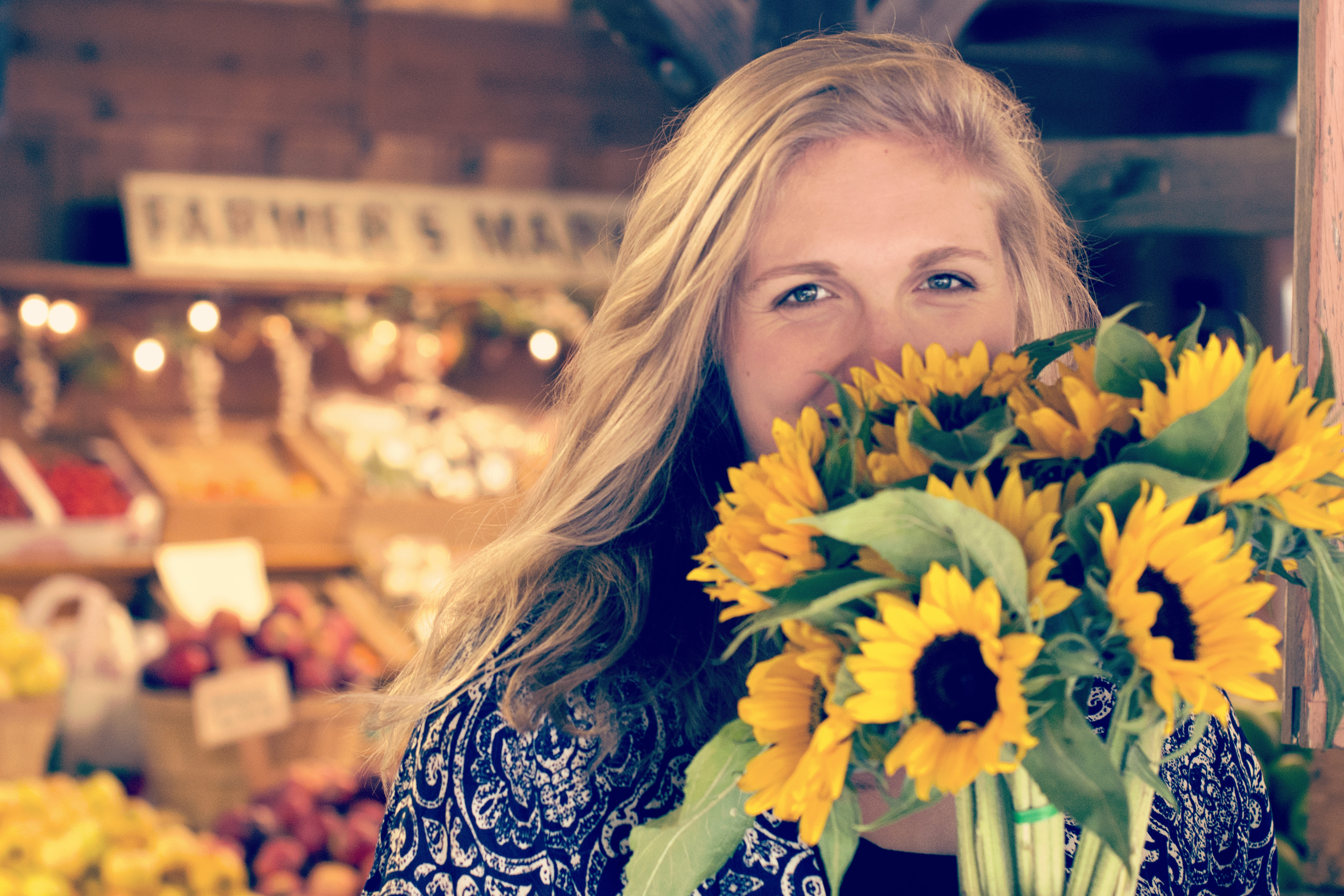 A woman in front of produce at Avila Valley Barn, holding a bouquet of sunflowers