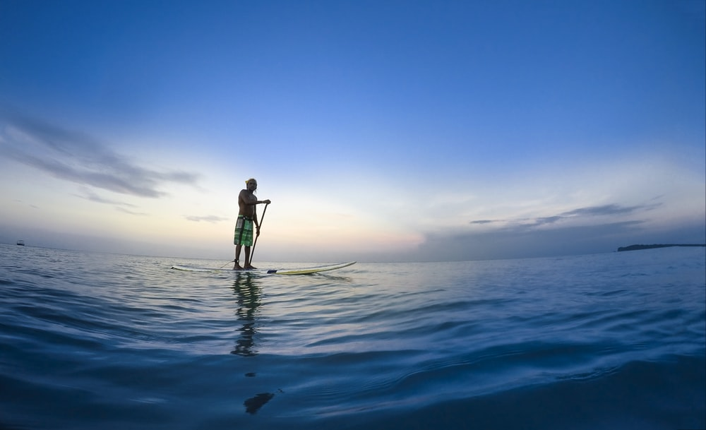 man standing on white paddle board holding paddle on body of water under blue sky