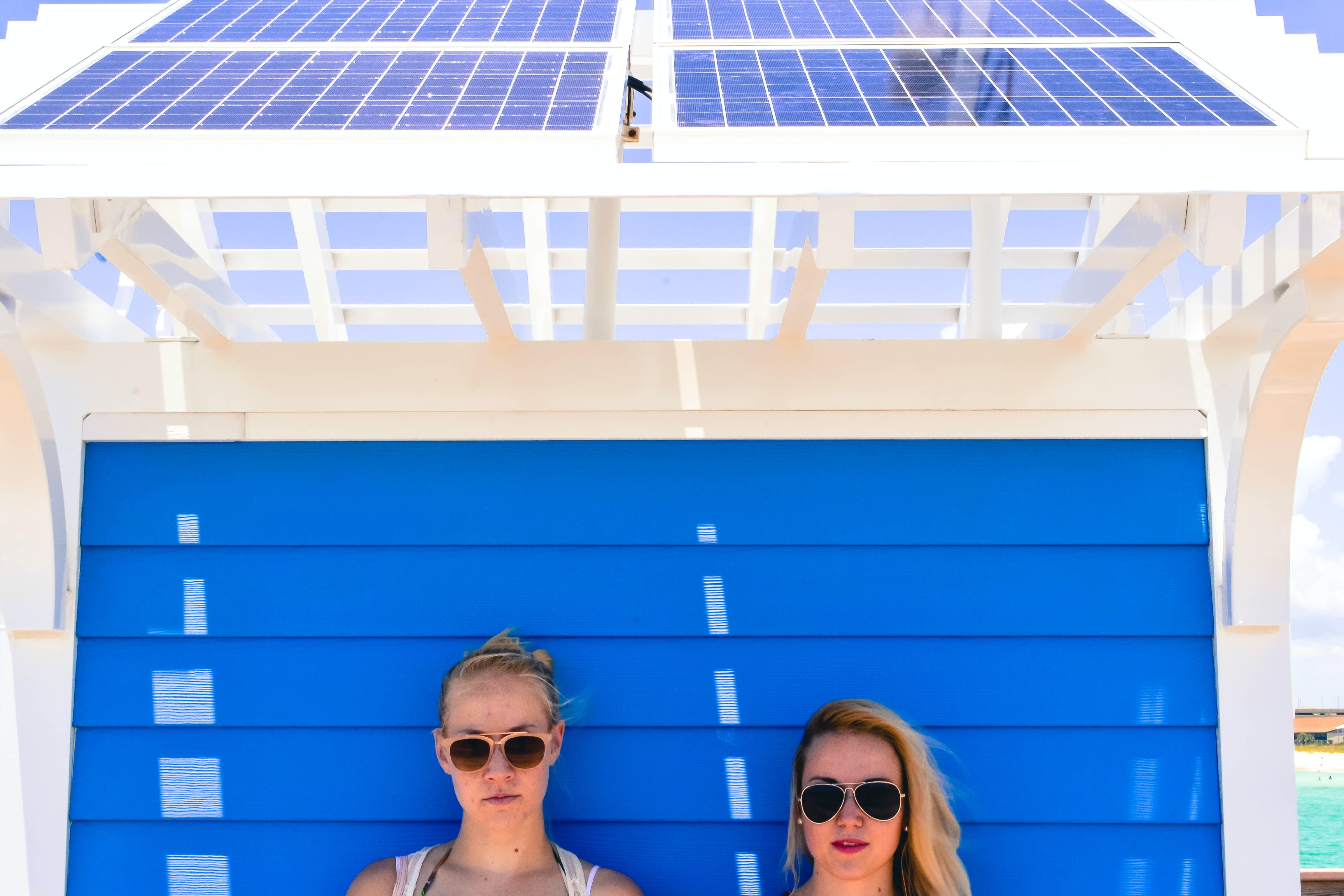 Two young women posing in front of blue wooden wall beneath solar cells at Panama City Beach