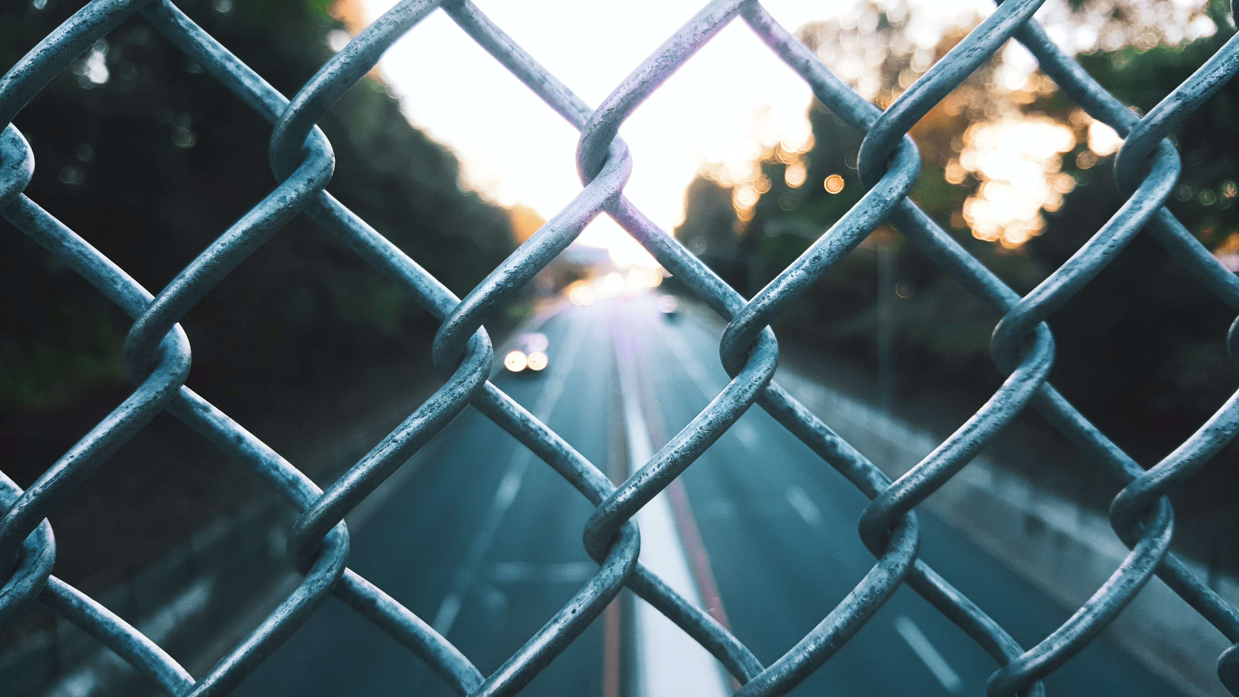 View through a chain-link fence on a two-lane road in Clifton