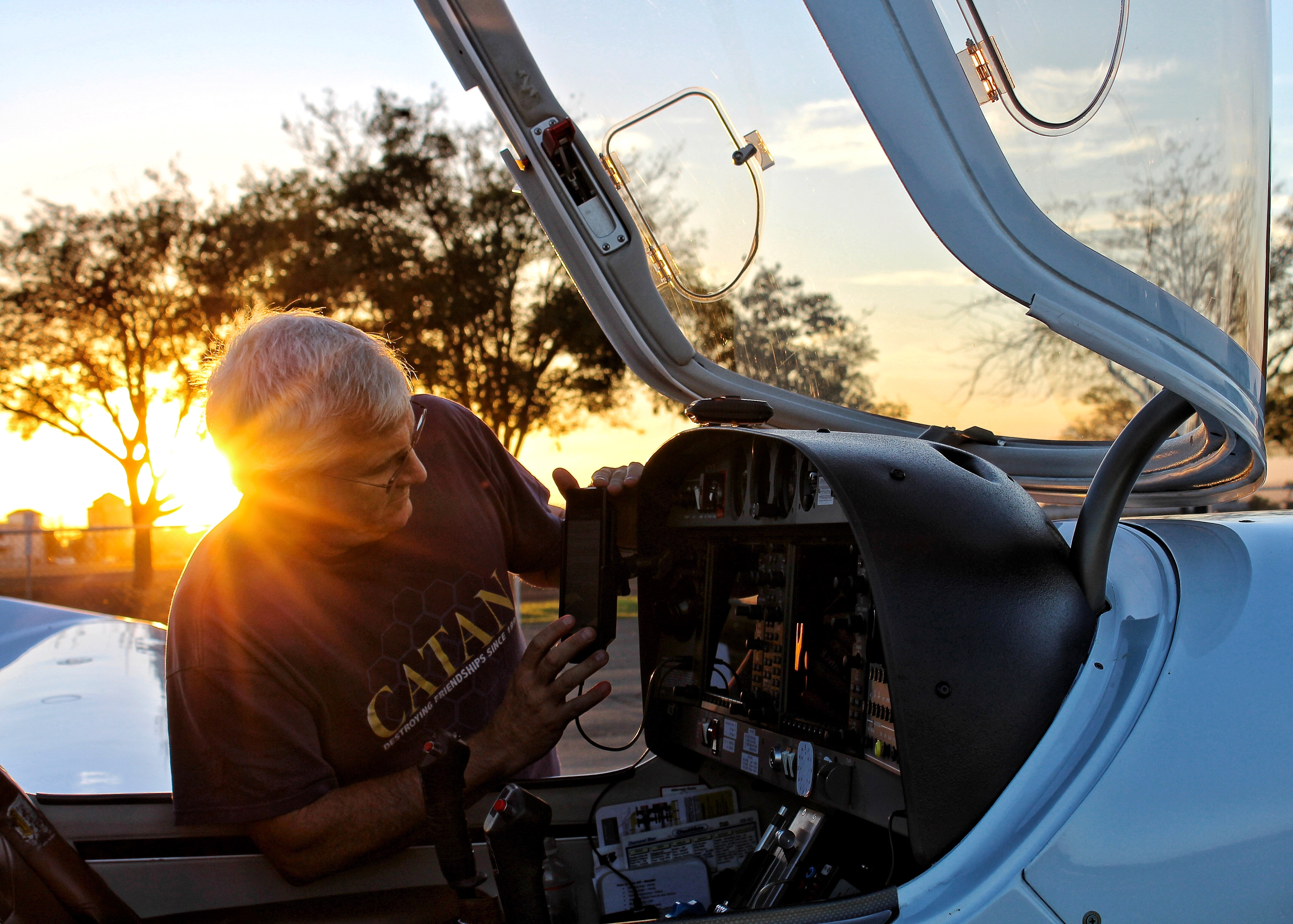 A man inspecting the equipment of a plane at Los Banos Municipal Airport during sunset